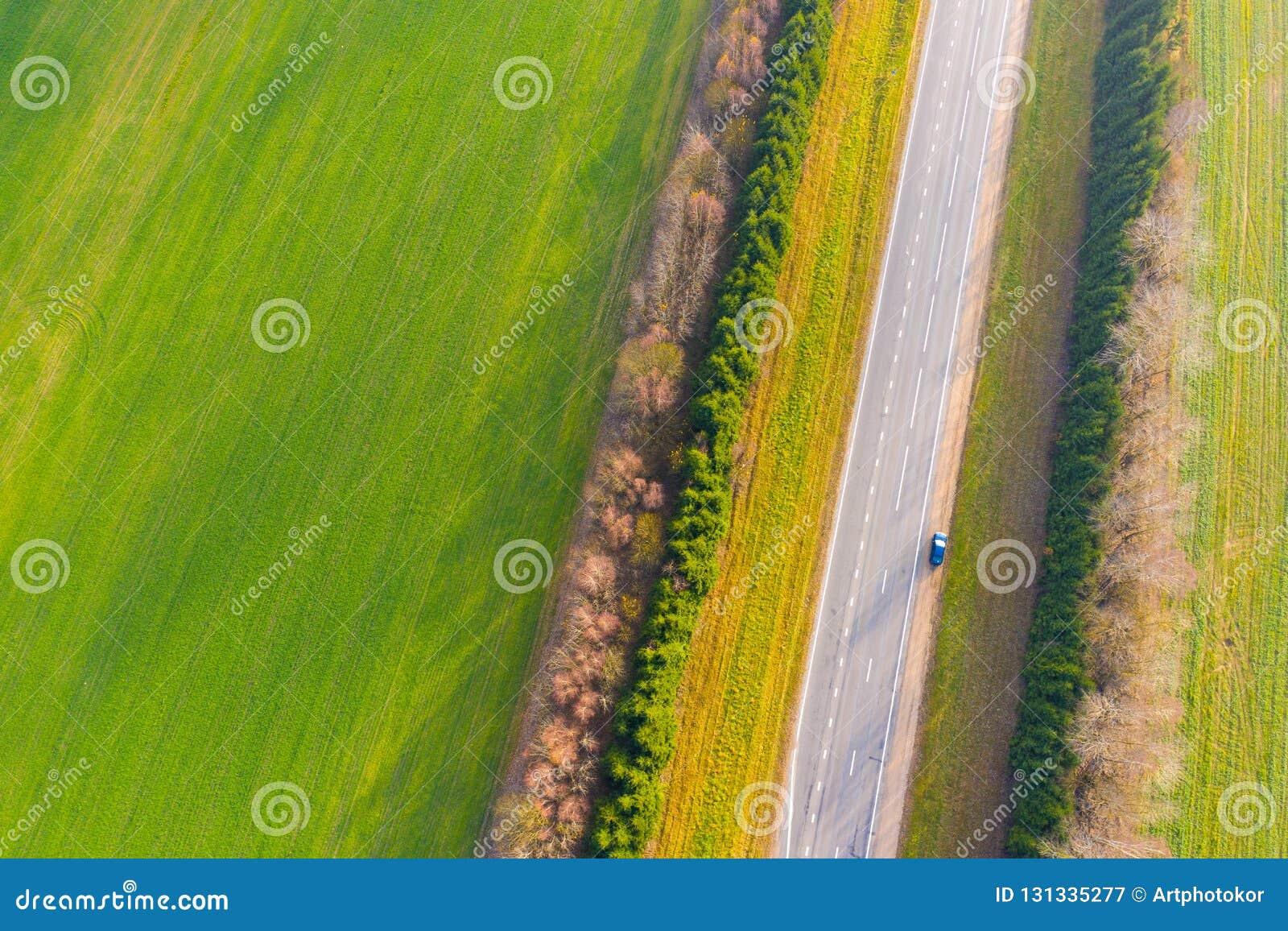 Carretera que va a lo largo de tierras de labrantío verdes Silueta del hombre de negocios Cowering