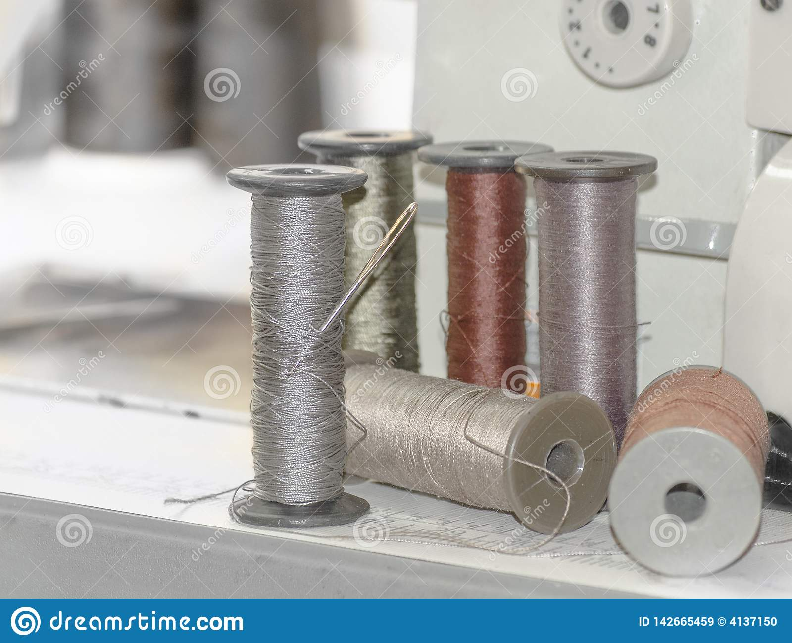 Carretes grandes del hilo en una máquina de coser