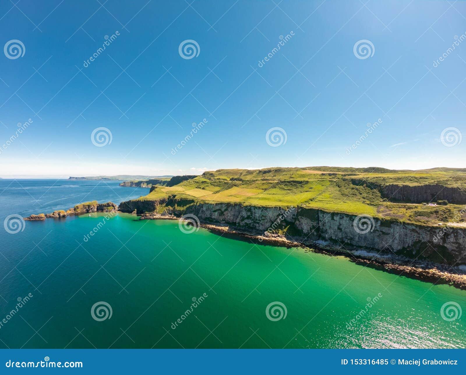 Carrick een Rede-Kabelbrug in Ballintoy Noord-Ierland Satellietbeeld op Klippen en het turkooise water van de Atlantische Oceaan