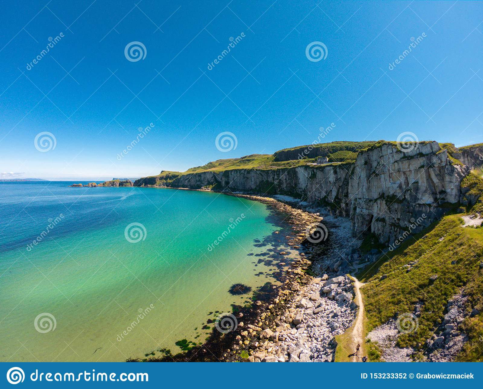 Carrick a Rede Rope Bridge in Ballintoy Northern Ireland. Aerial view on Cliffs and turquoise Atlantic Ocean water