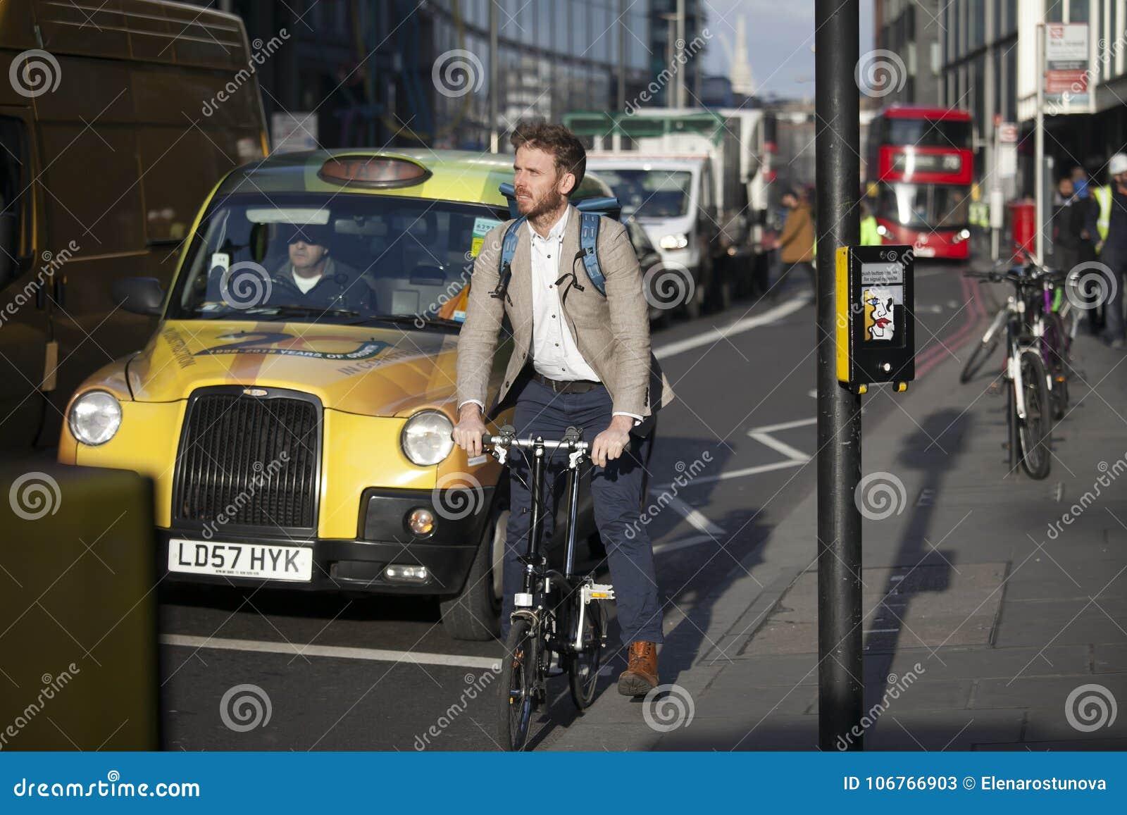 Carril del ladrillo de la calle al mediodía en el contraluz Prisa de la gente sobre su negocio Un hombre que monta una bicicleta