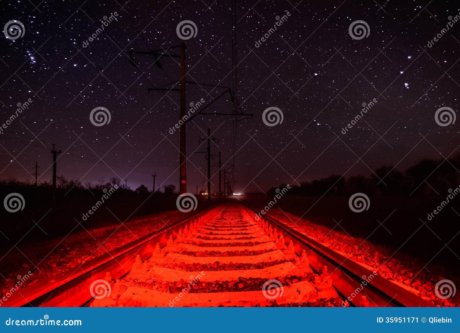 Carriles contra el cielo estrellado con la iluminación roja inusual