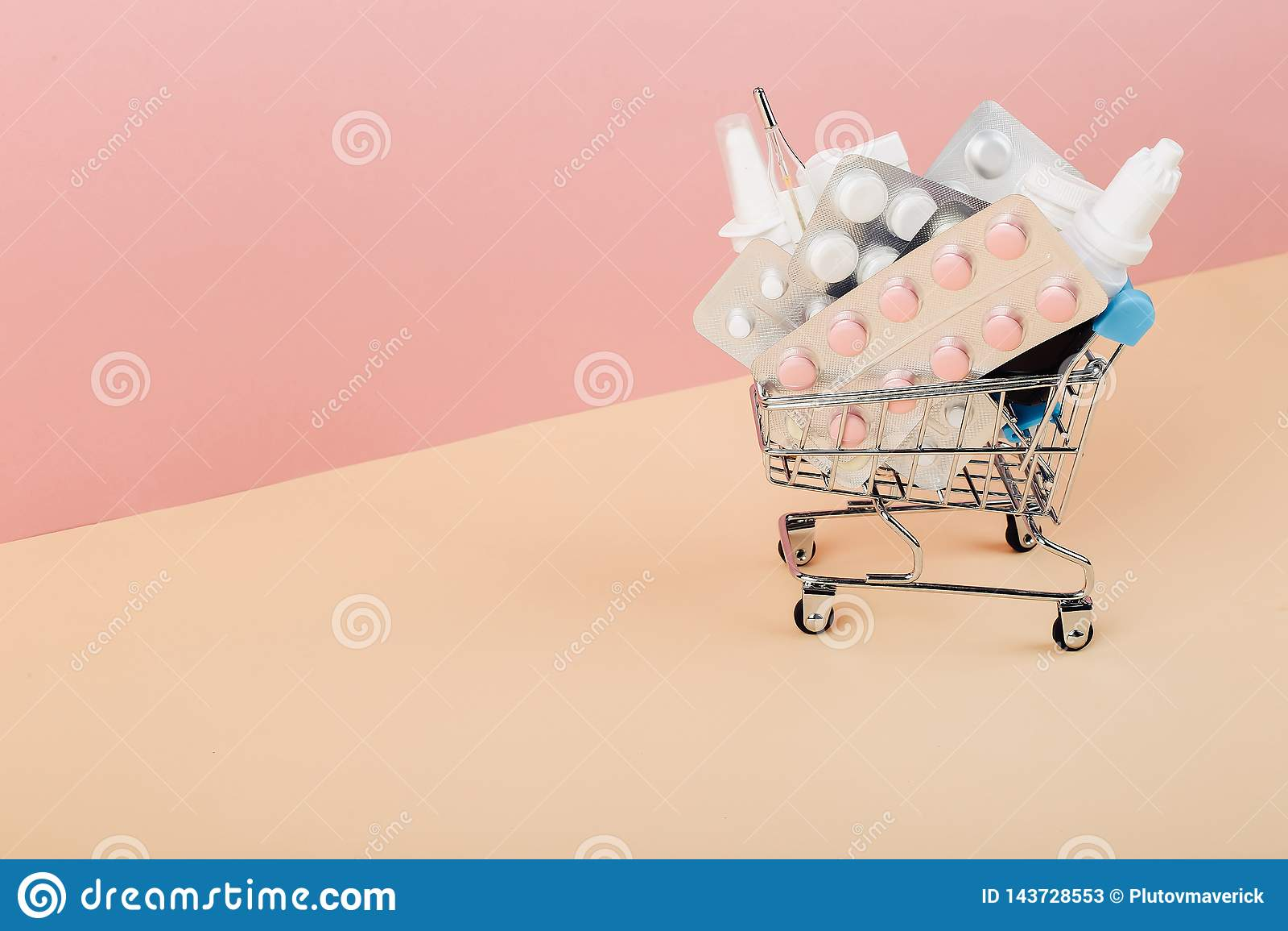 Carrinho de compras carregado com os comprimidos em um fundo amarelo cor-de-rosa O conceito da medicina e a venda das drogas Copi