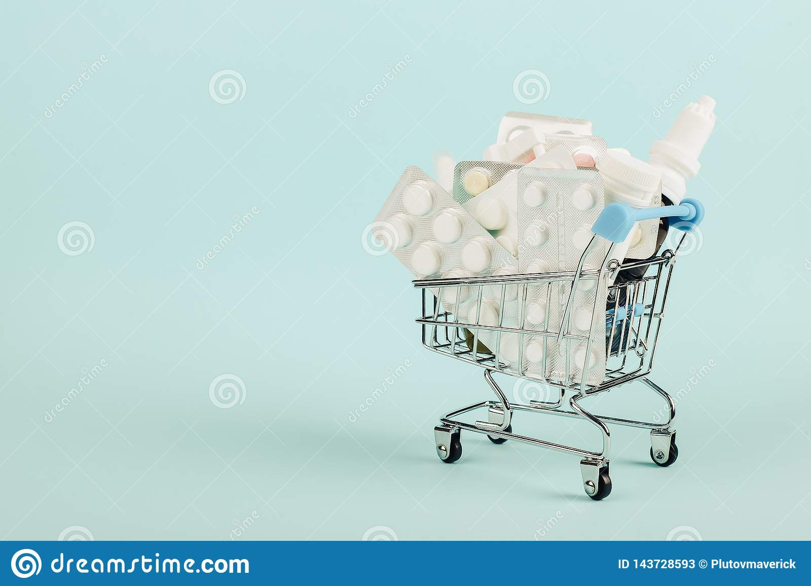Carrinho de compras carregado com os comprimidos em um fundo azul O conceito da medicina e a venda das drogas Copie o espaço