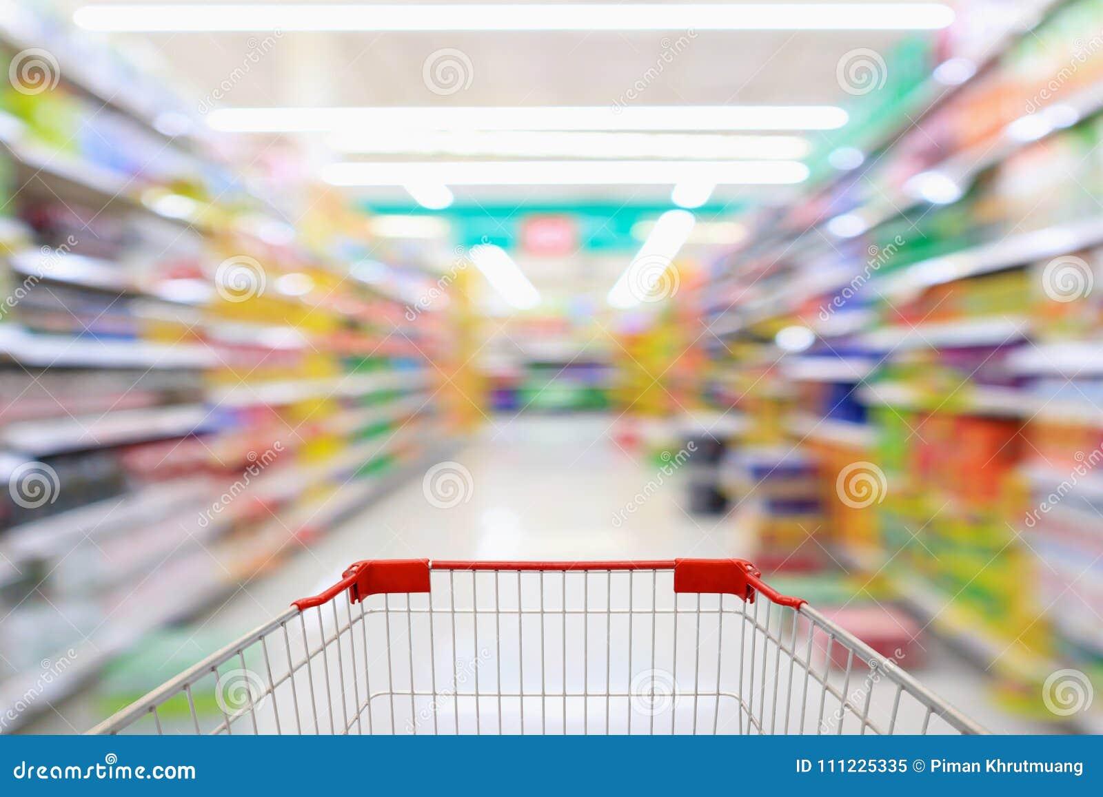 Carrinho de compras com fundo do borrão do corredor do supermercado