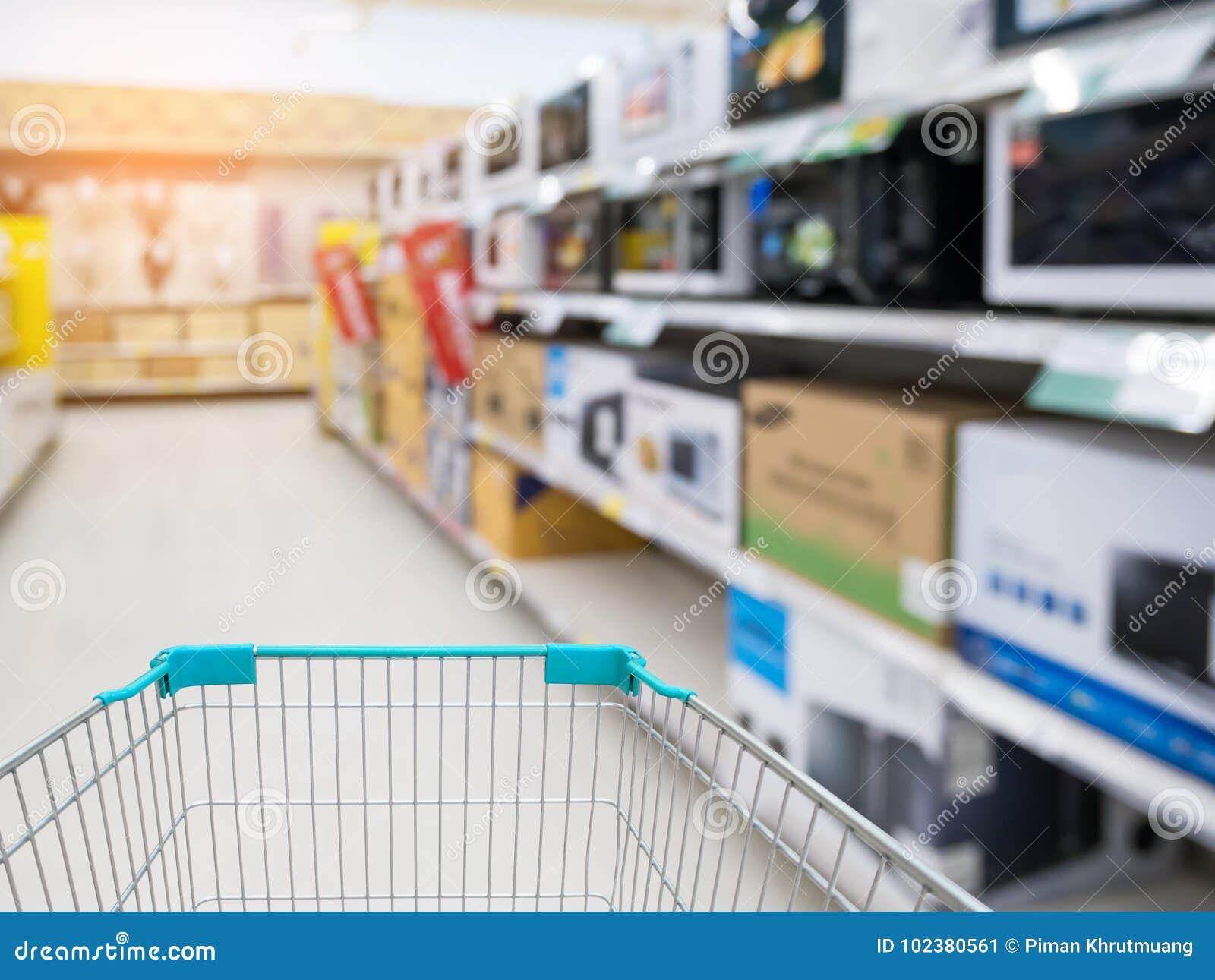 Carrinho de compras com o corredor da loja da eletrônica do borrão