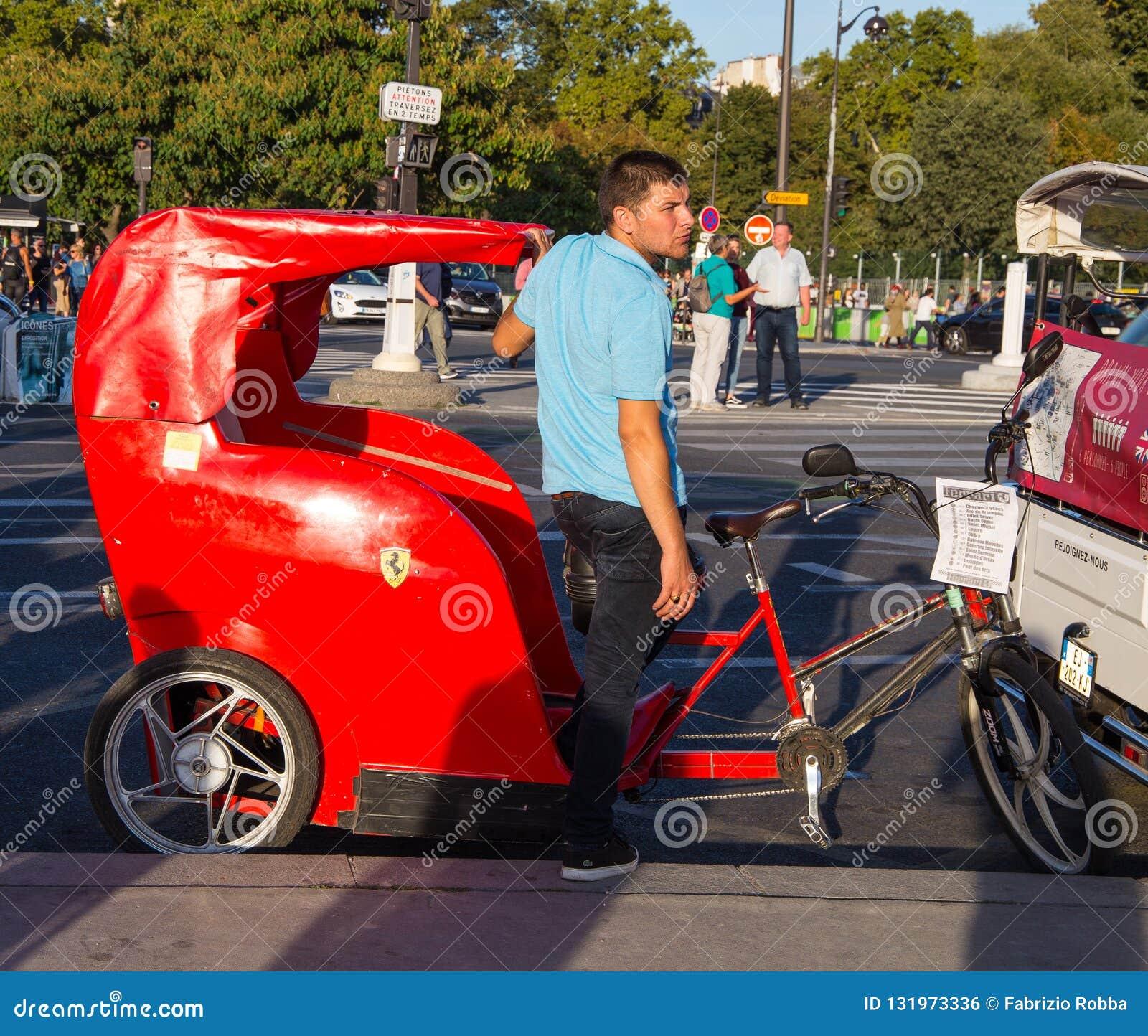 Carrito rojo para los turistas con el logotipo del coche de Ferrari cerca de la torre Eiffel en París, Francia