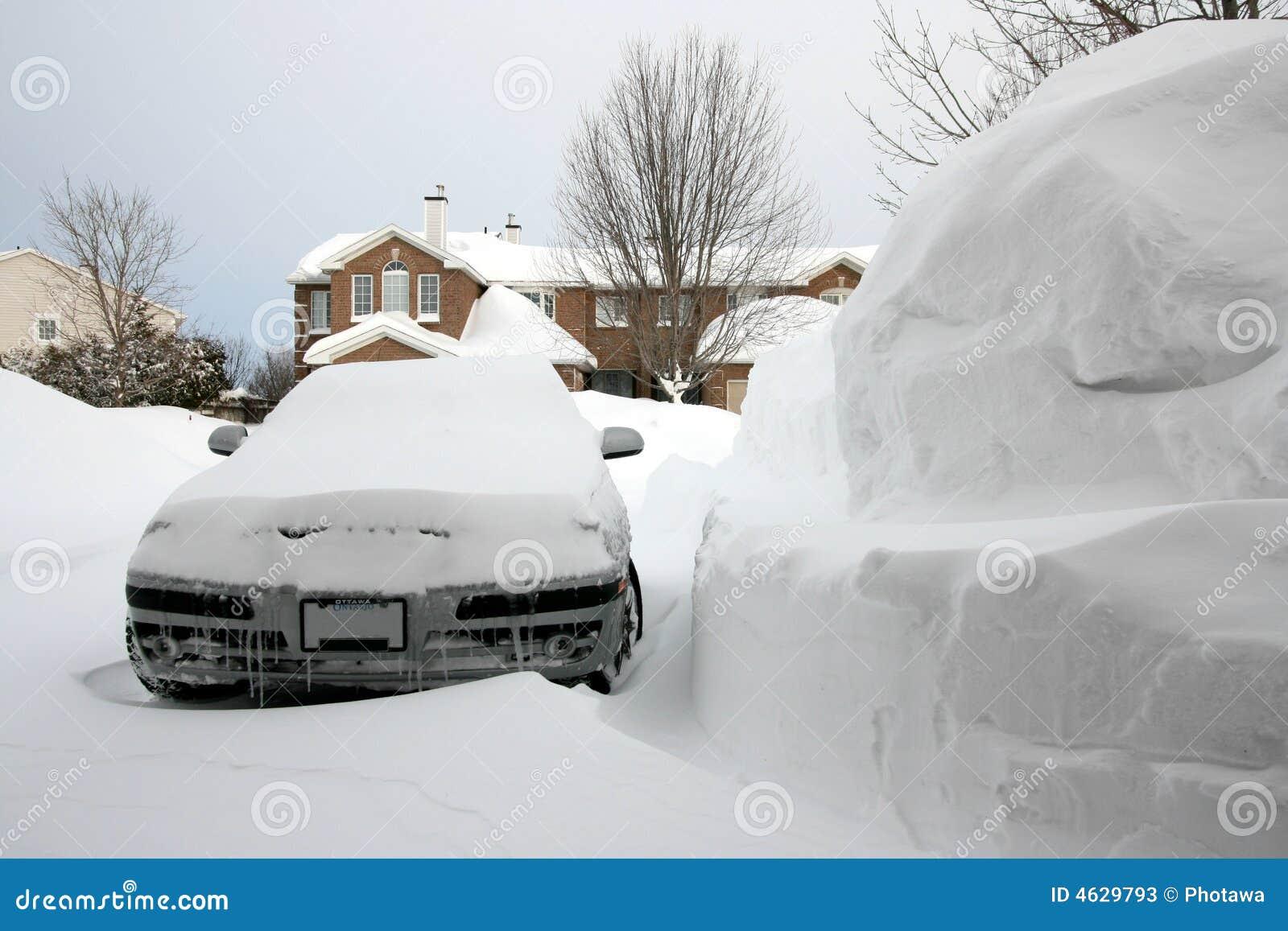 Carro ao lado da pilha enorme da neve