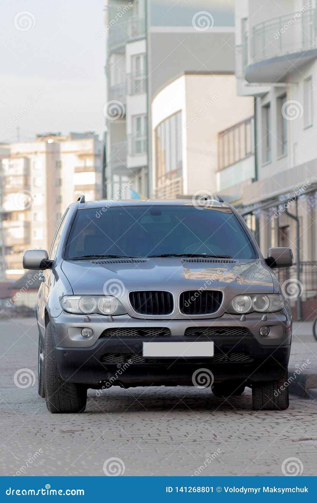 Carro cinzento caro novo estacionado no parque de estacionamento pavimentado na parte dianteira Conceito do transporte e do estac