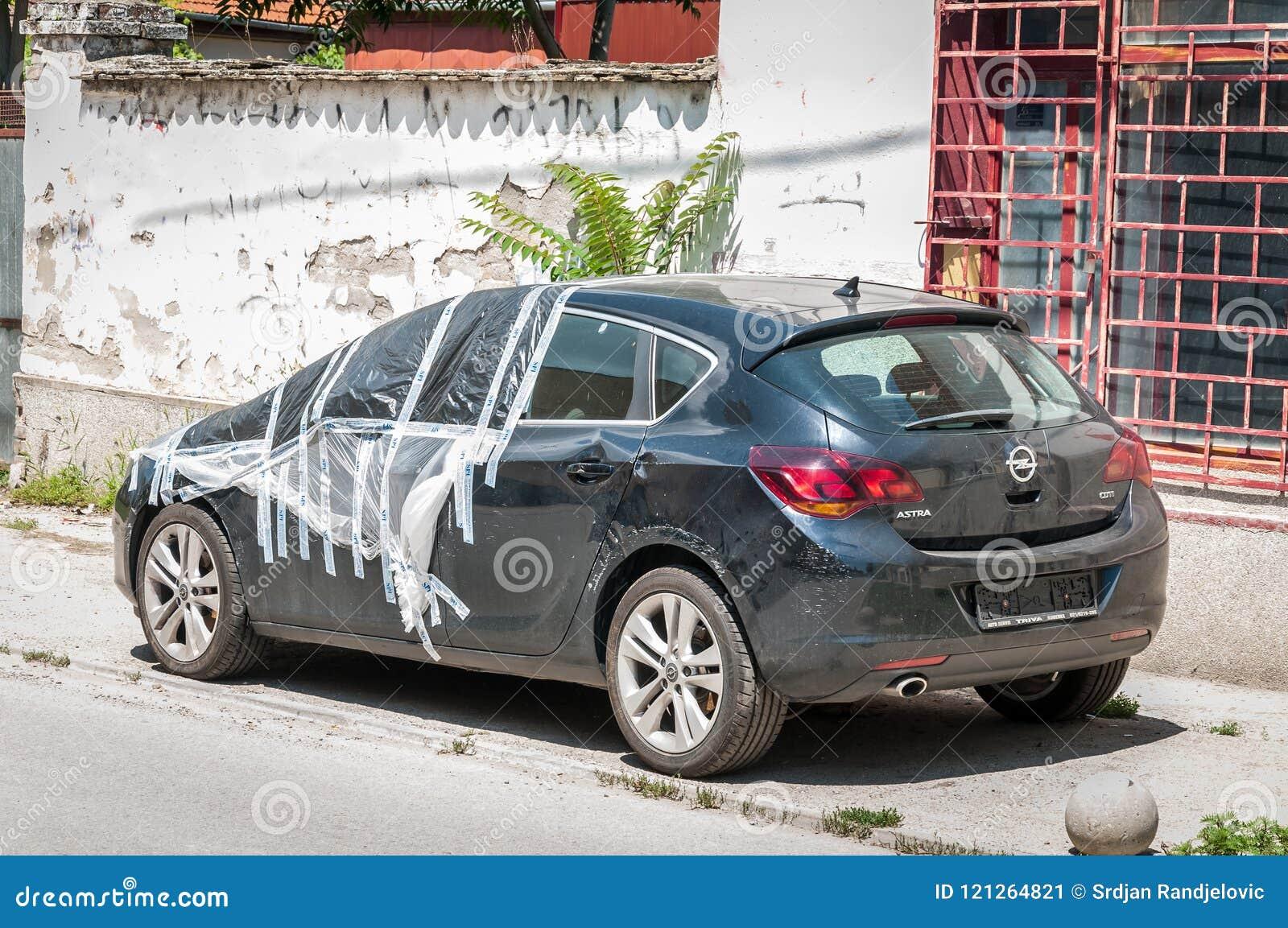 Carro Com Porta Traseira Preto Novo Danificado De Opel Astra J Estacionado Na Rua Coberta E Protegida Com Nylon Sobre O Para Bris Foto Editorial Imagem De Astra Opel 121264821