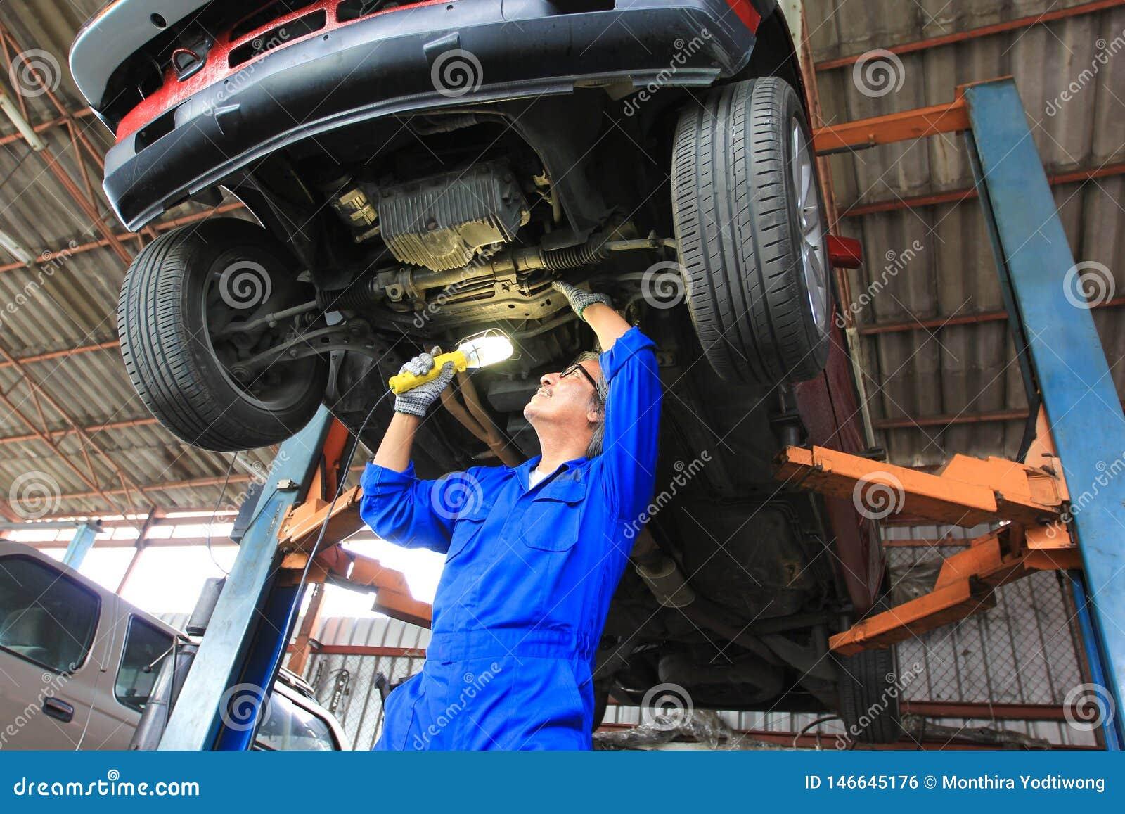Carro de exame do mec?nico de carro usando a lanterna el?trica no servi?o de repara??o de autom?veis