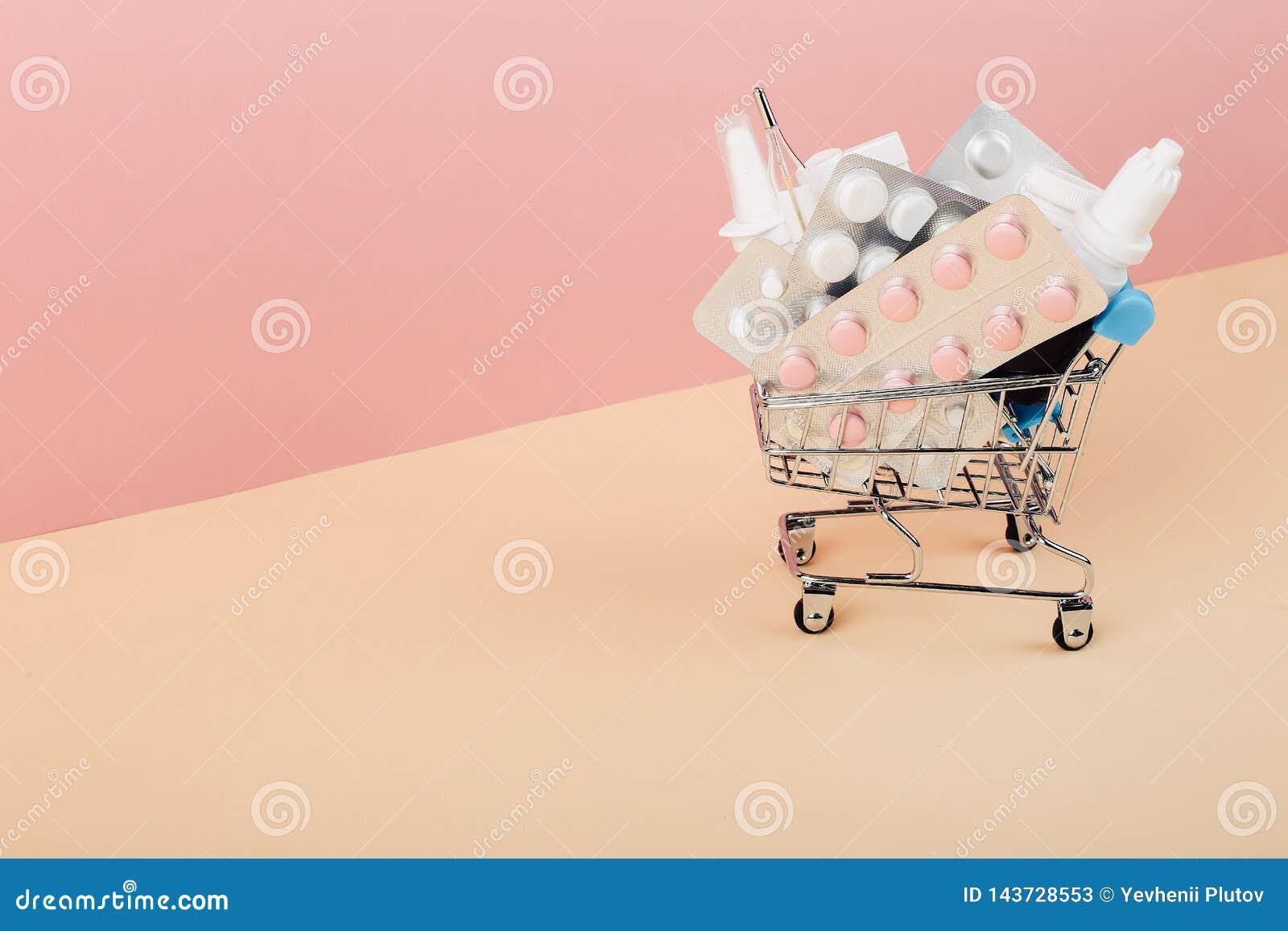 Carro de la compra cargado con las píldoras en un fondo amarillo rosado El concepto de medicina y la venta de drogas Copie el esp