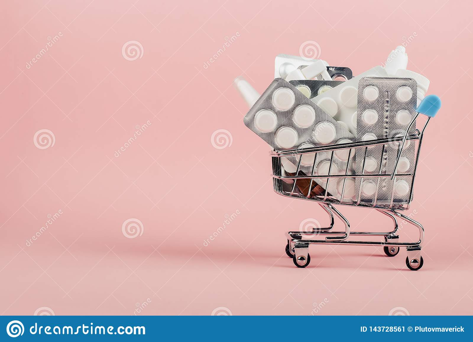 Carro de la compra cargado con las píldoras en un fondo rosado El concepto de medicina y la venta de drogas Copie el espacio