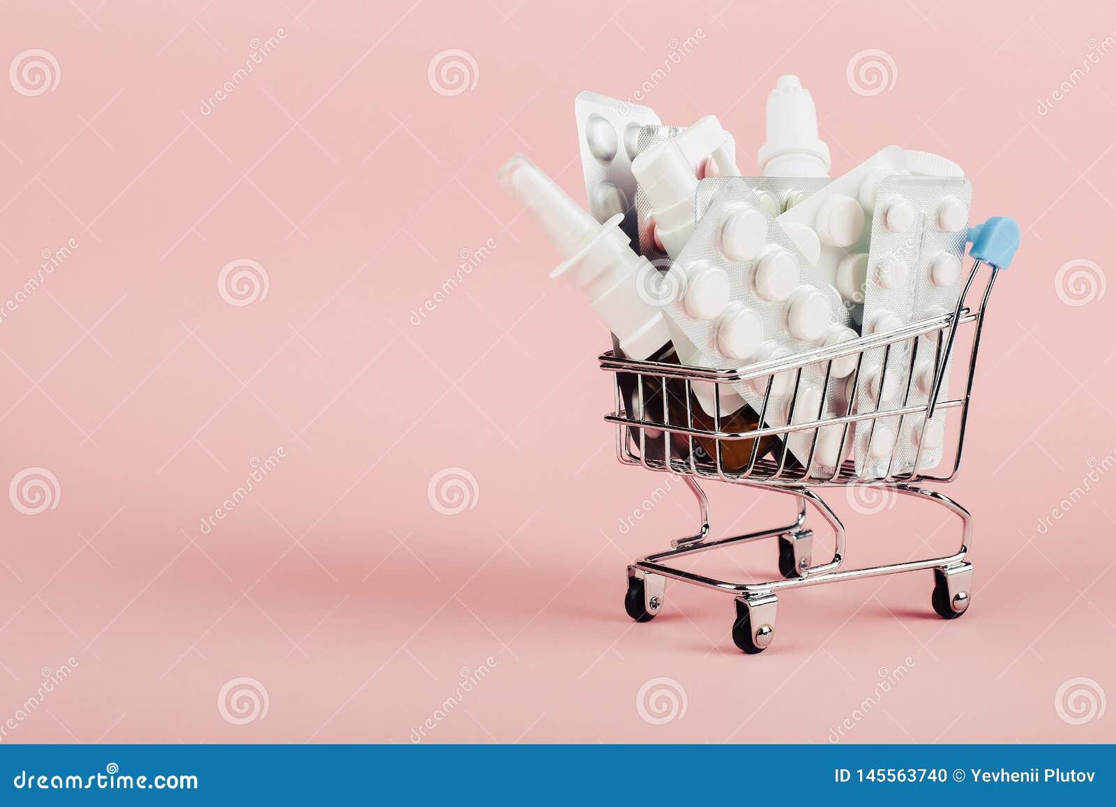 Carro de la compra cargado con las p?ldoras en un fondo rosado El concepto de medicina y la venta de drogas Copie el espacio