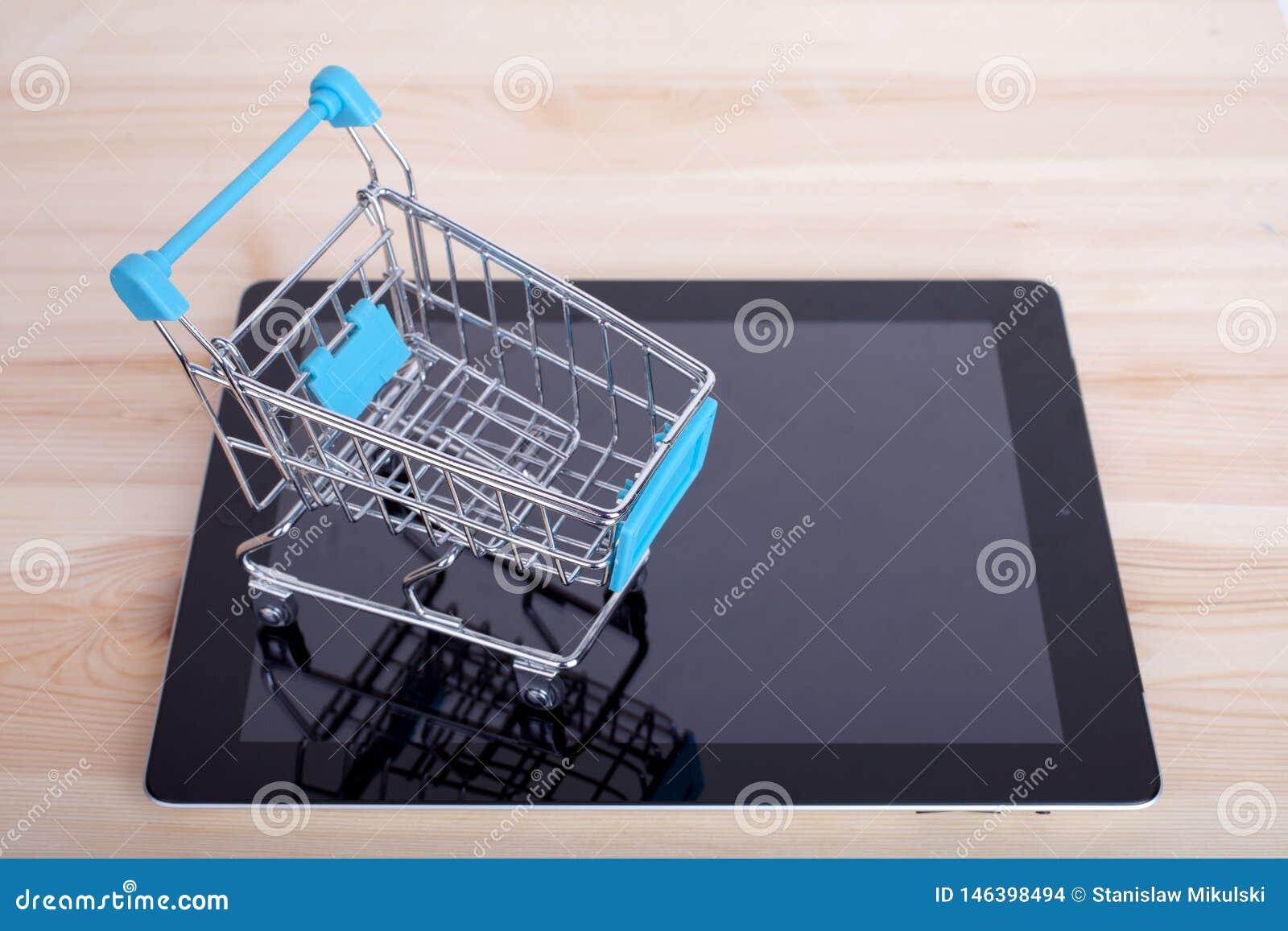 Carro de la compra sobre un Tablet PC en la tabla de madera