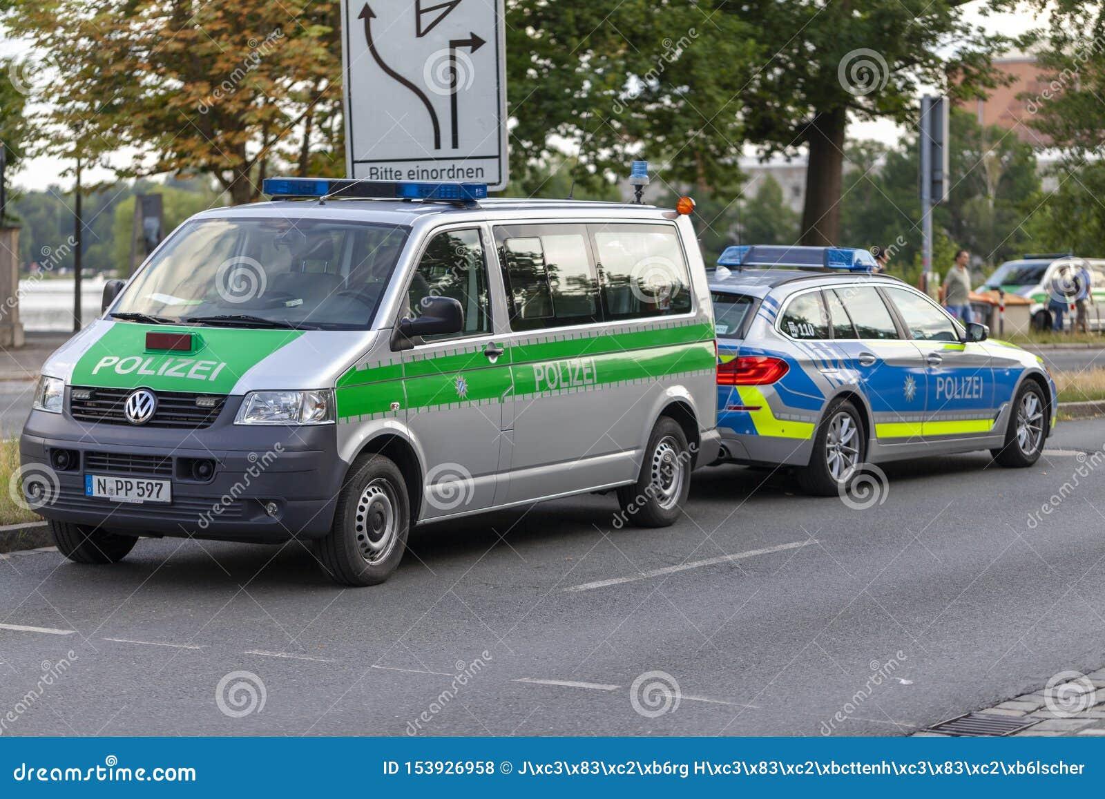 Carro de polícia dos suportes alemães da polícia em uma rua