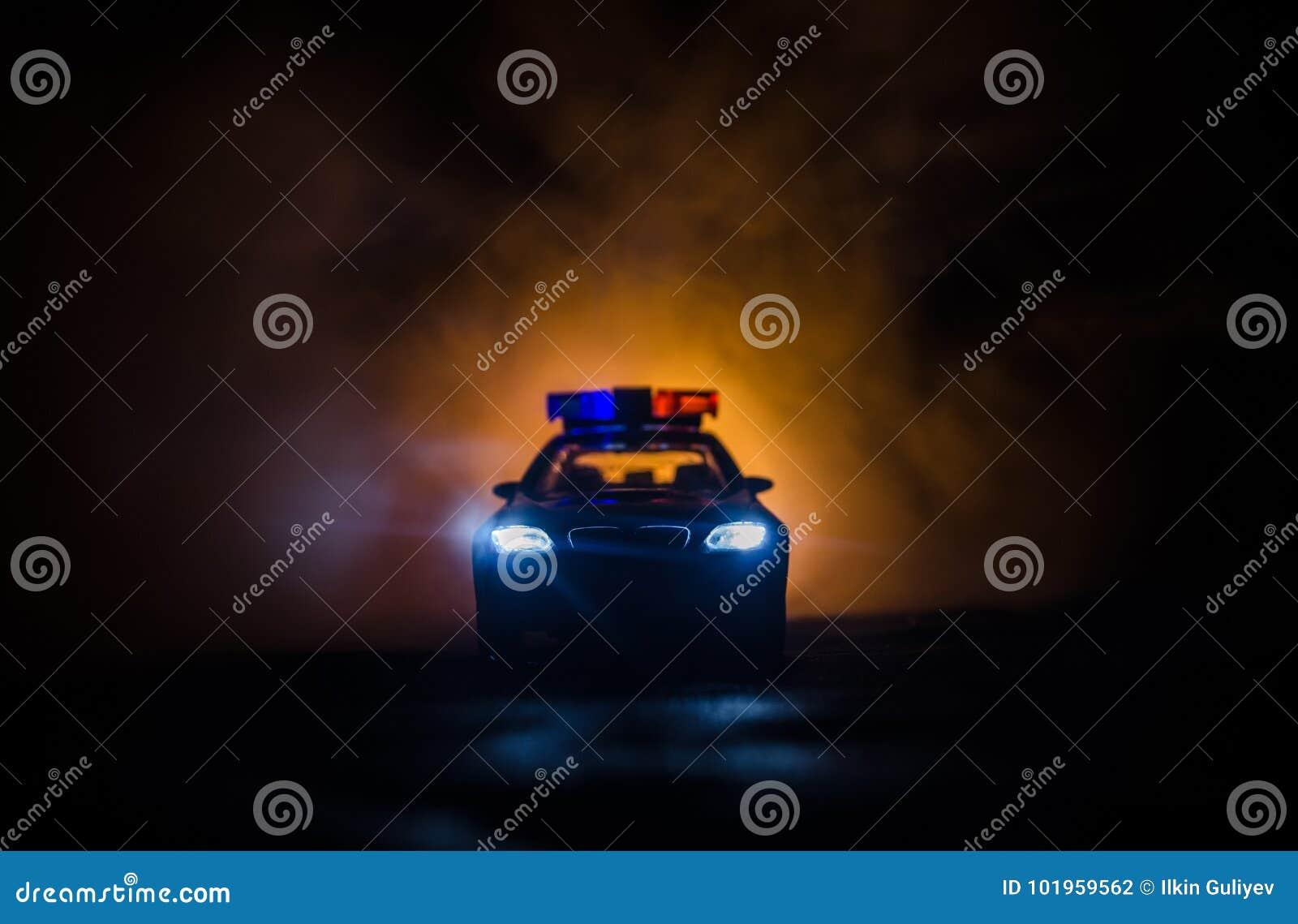 Carro de polícia que persegue um carro na noite com fundo da névoa Carro de 911 polícias da resposta de emergencia que apressa-se