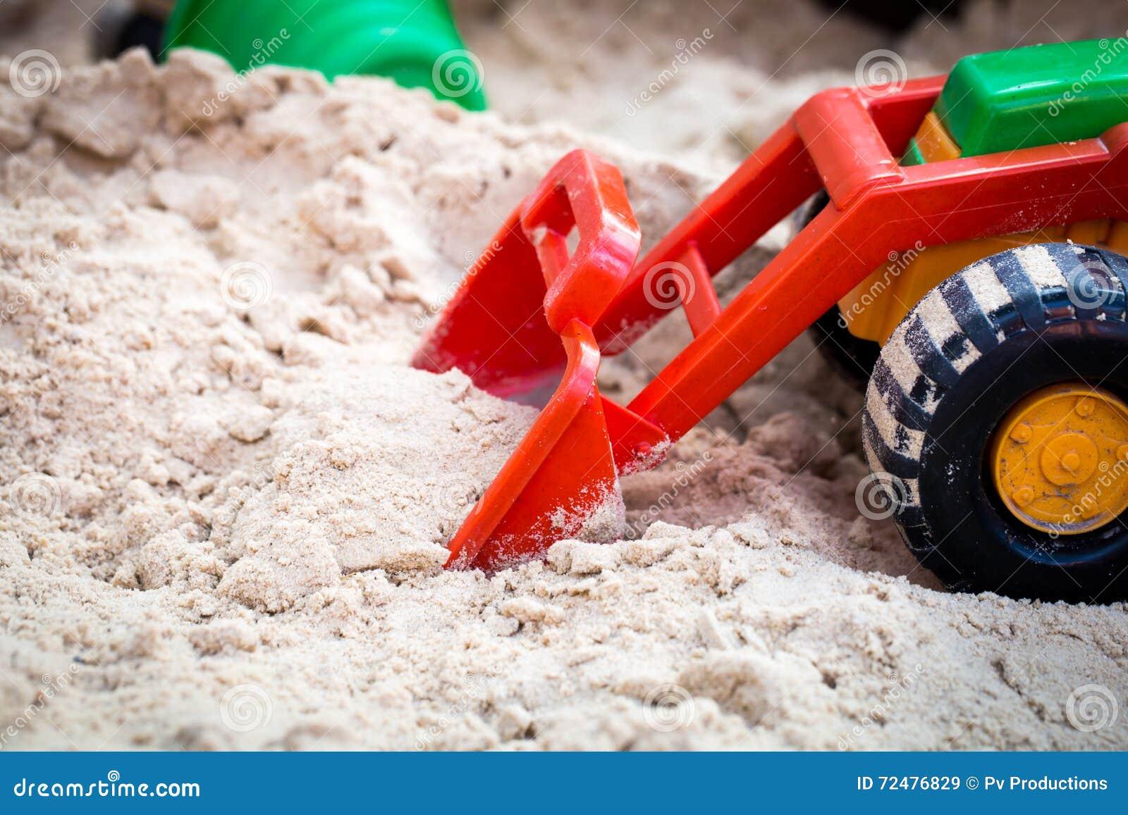 Carro do brinquedo das crianças na caixa de areia