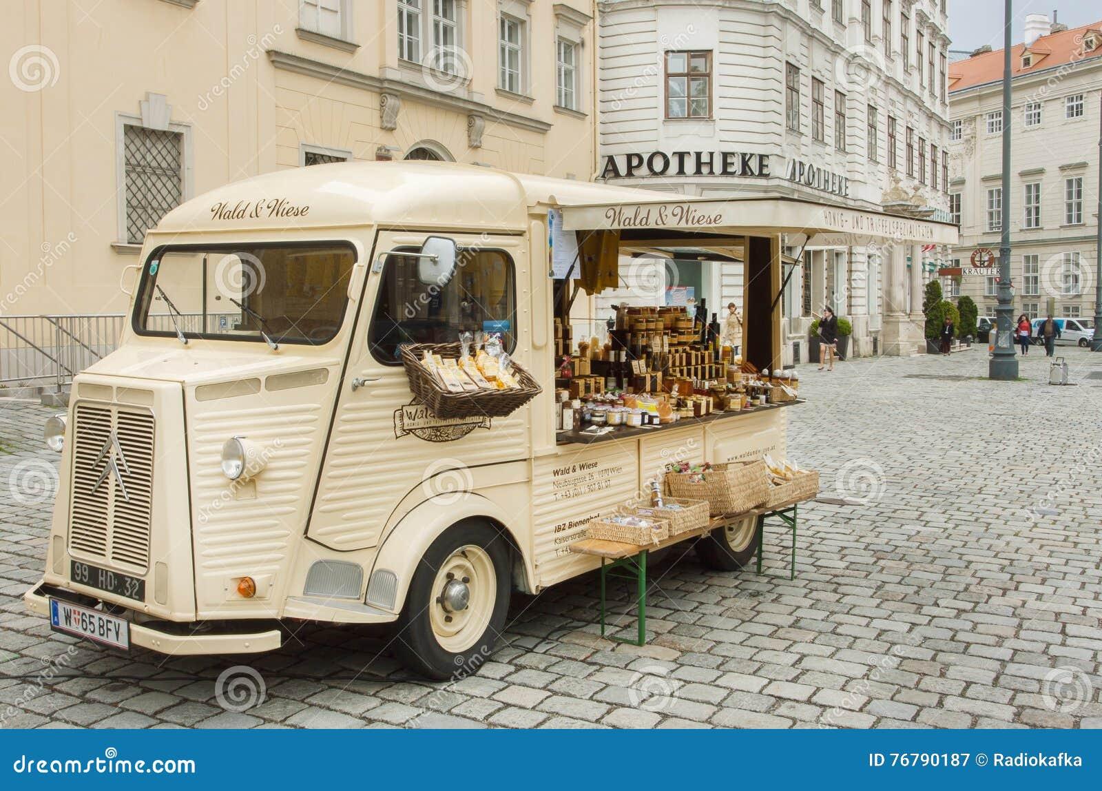 Carro do vintage com mostra, alimento e cosméticos do comerciante para a venda exterior