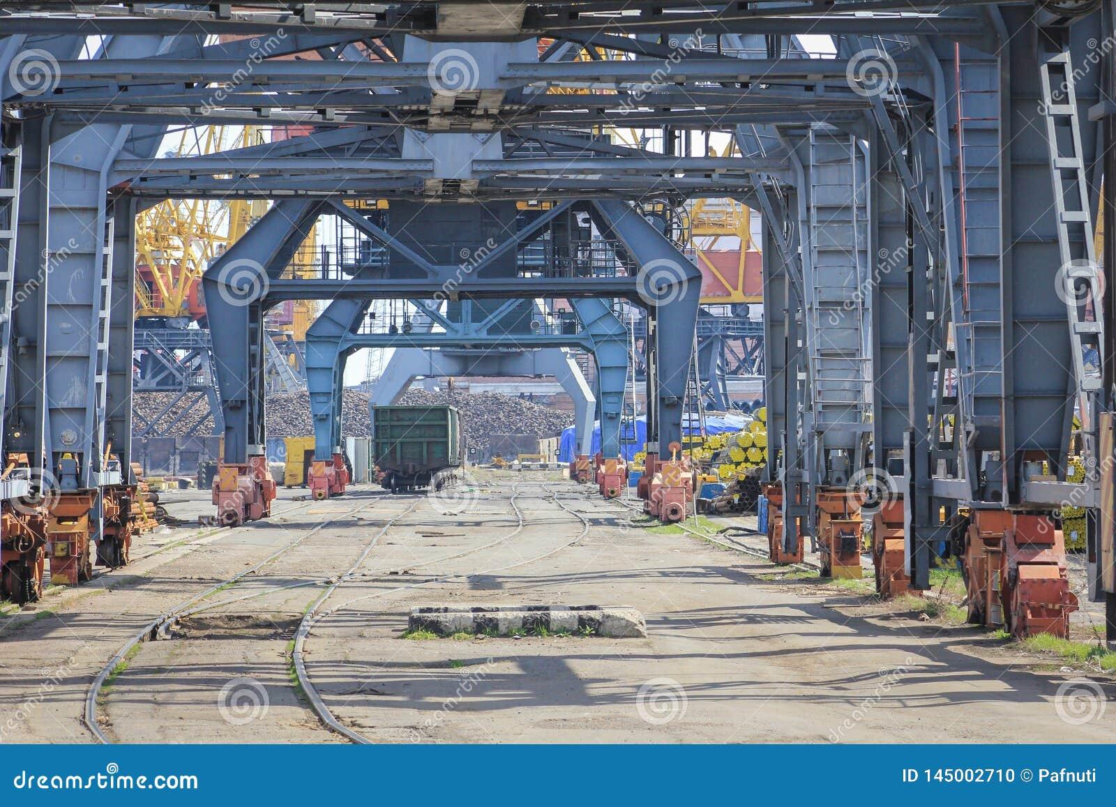 Carro ferroviario debajo de las gr?as cargadas en puerto mar?timo