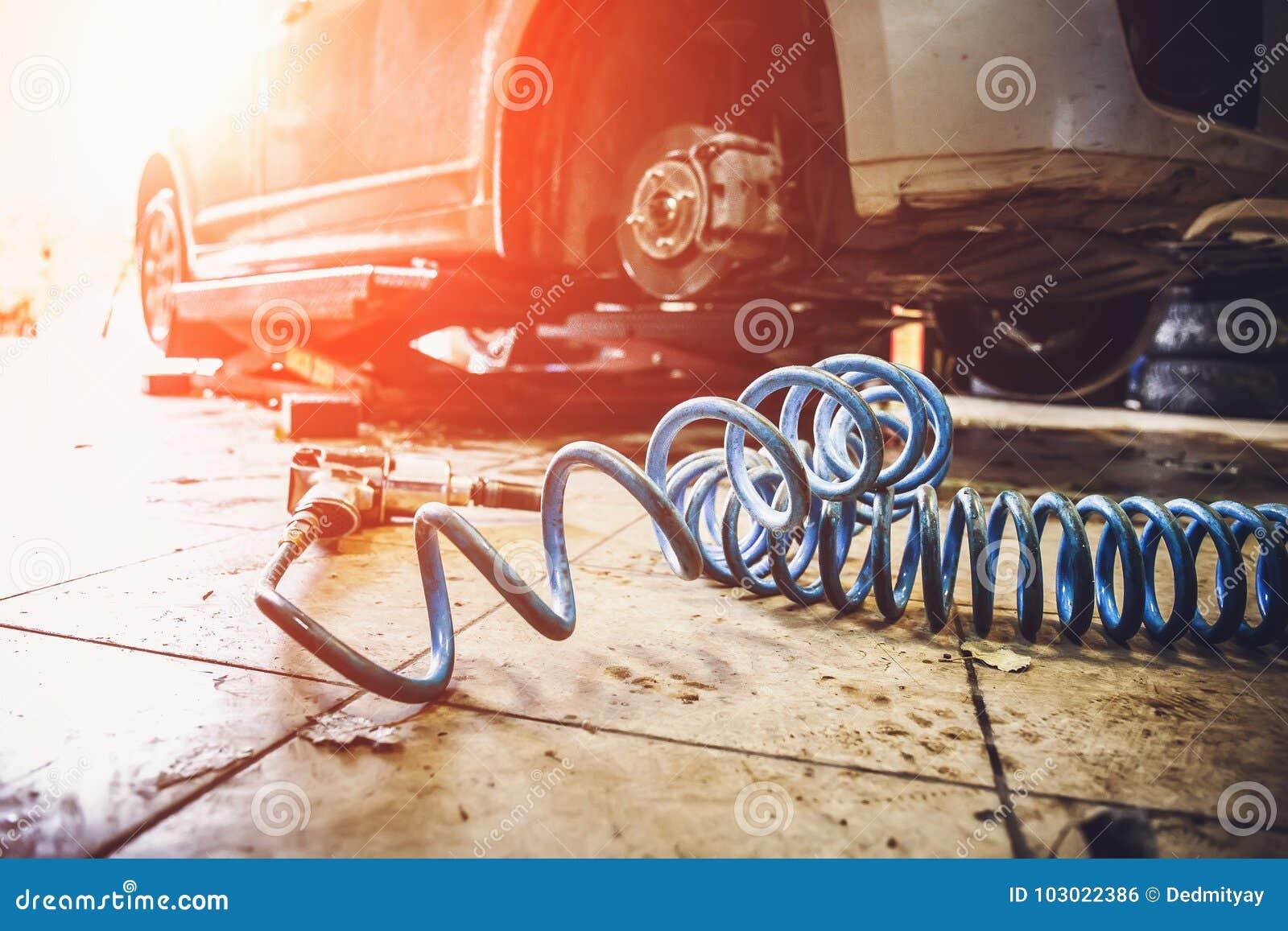 Carro na garagem na oficina do serviço de reparações do auto mecânico com a máquina especial que repara o equipamento