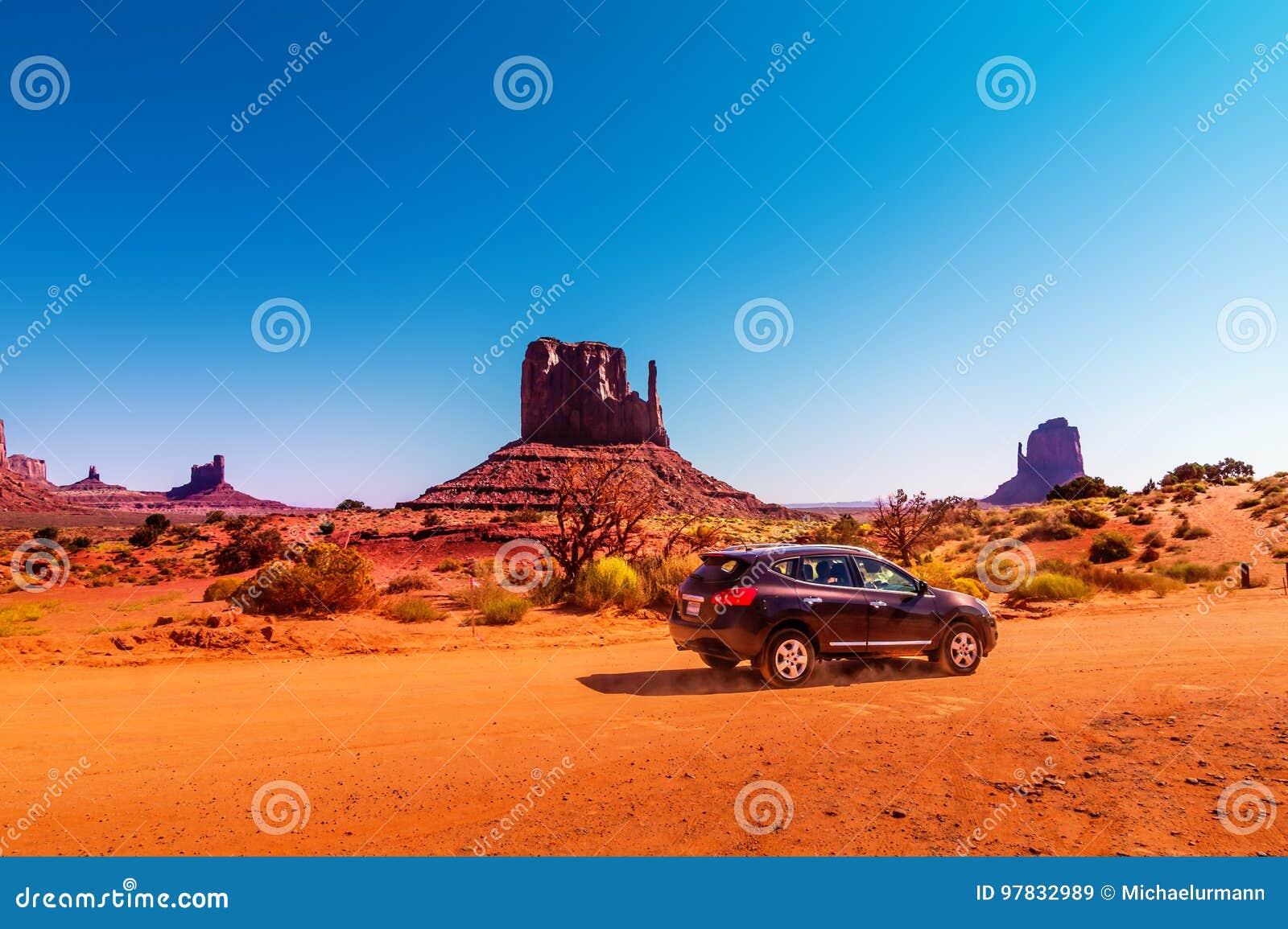 Carro na movimentação do vale do monumento A movimentação do vale é uma estrada de terra cênico através do parque tribal do Navaj