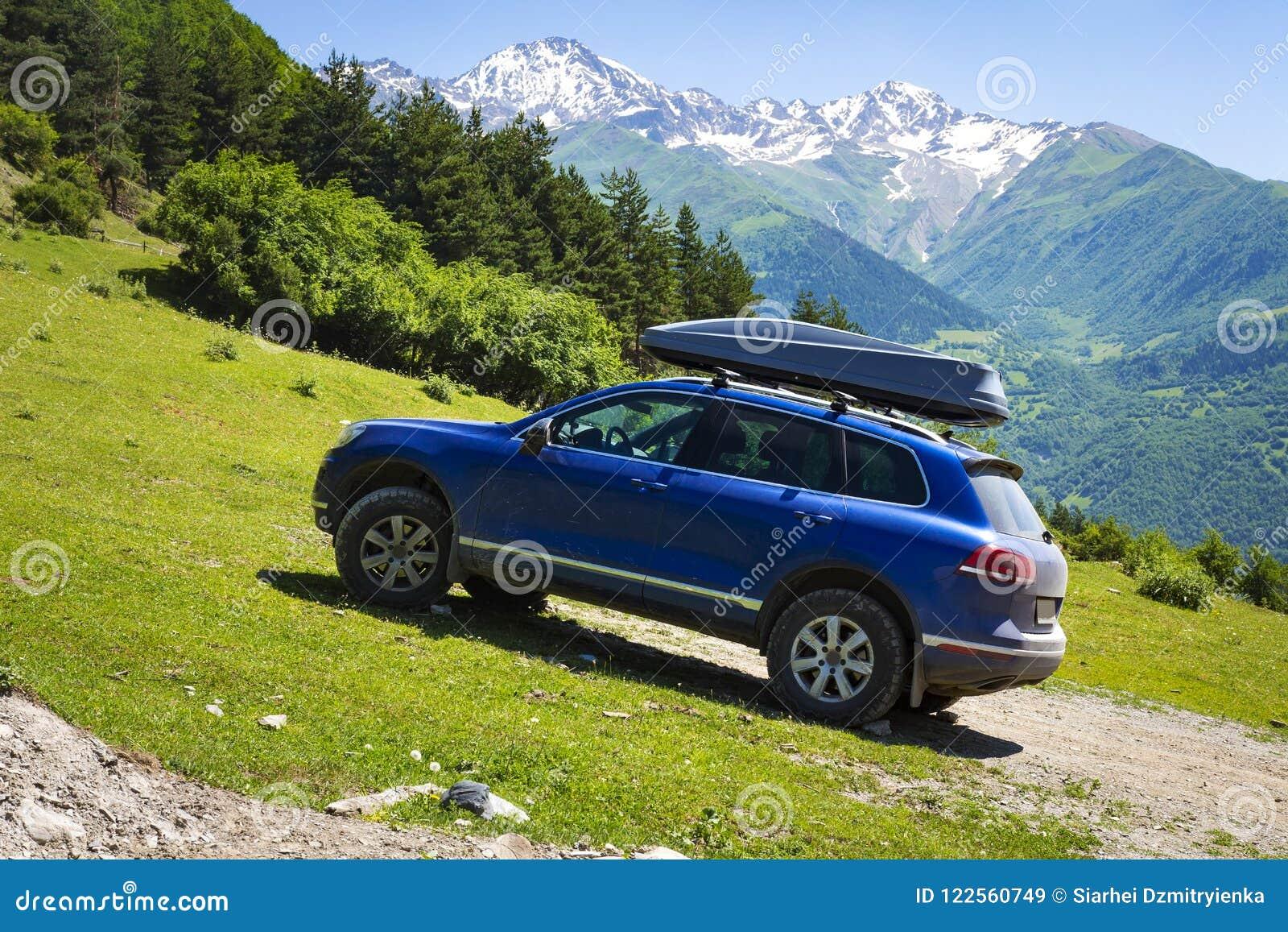 Carro nas montanhas O carro é um carro fora de estrada na montanha no dia de verão claro, ensolarado Curso pelo carro com o selva