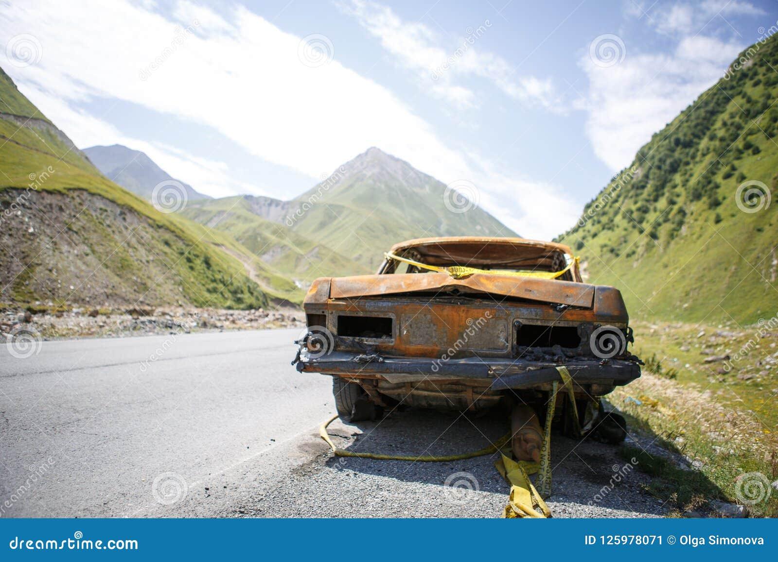 Carro queimado oxidado velho na borda da estrada de Geórgia, cercada por montanhas e por beleza