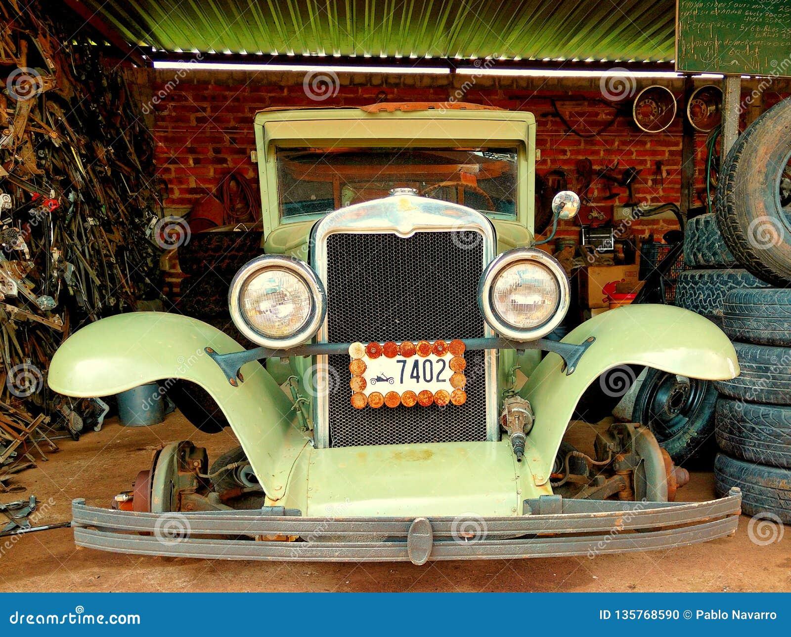 Carro velho nostálgico sob o reparo dentro de uma garagem