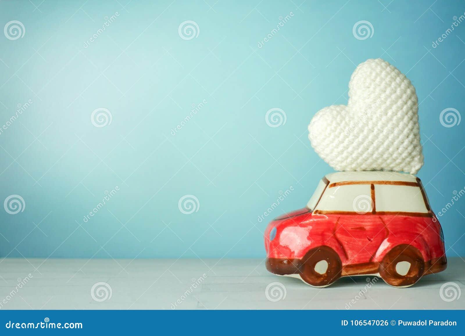Carro vermelho diminuto que leva um coração branco no fundo ciano