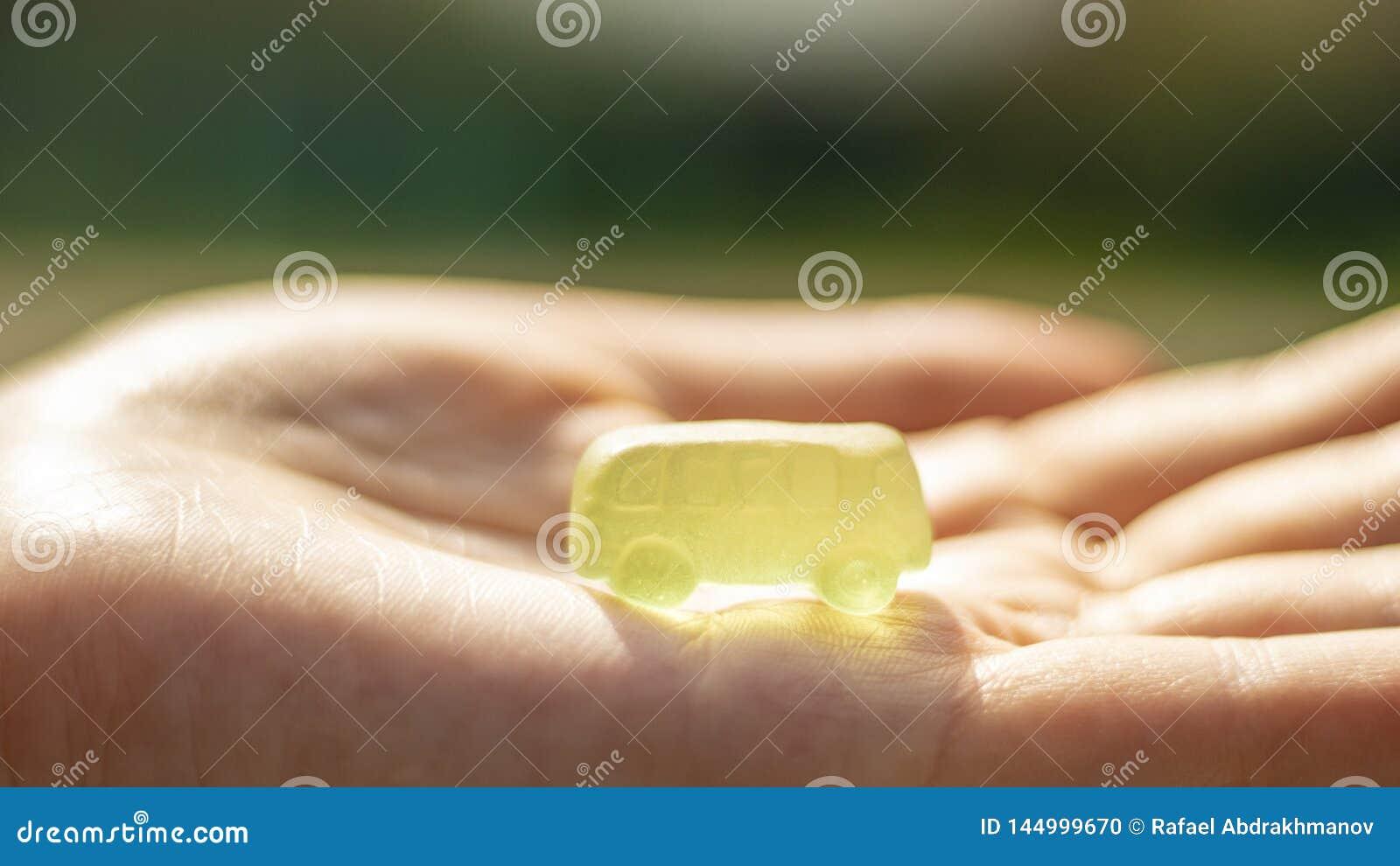 Carros comest?veis coloridos do doce de fruta em uma palma das crian?as Ideia do neg?cio para obter um empr?stimo da hipoteca ou