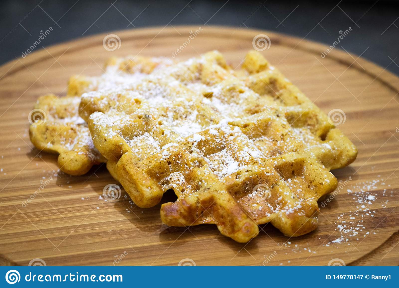 Carrot waffles with powdered sugar on a wooden boardPerfect healthy breakfast