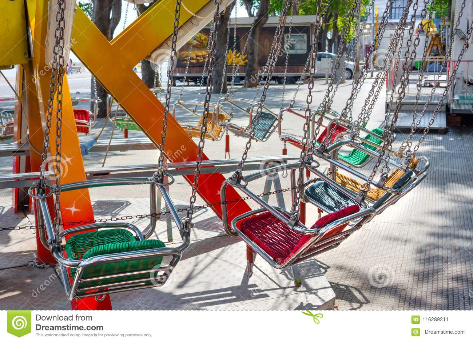 Carrousel vide de siège d enfant sur des chaînes dans le jour d été