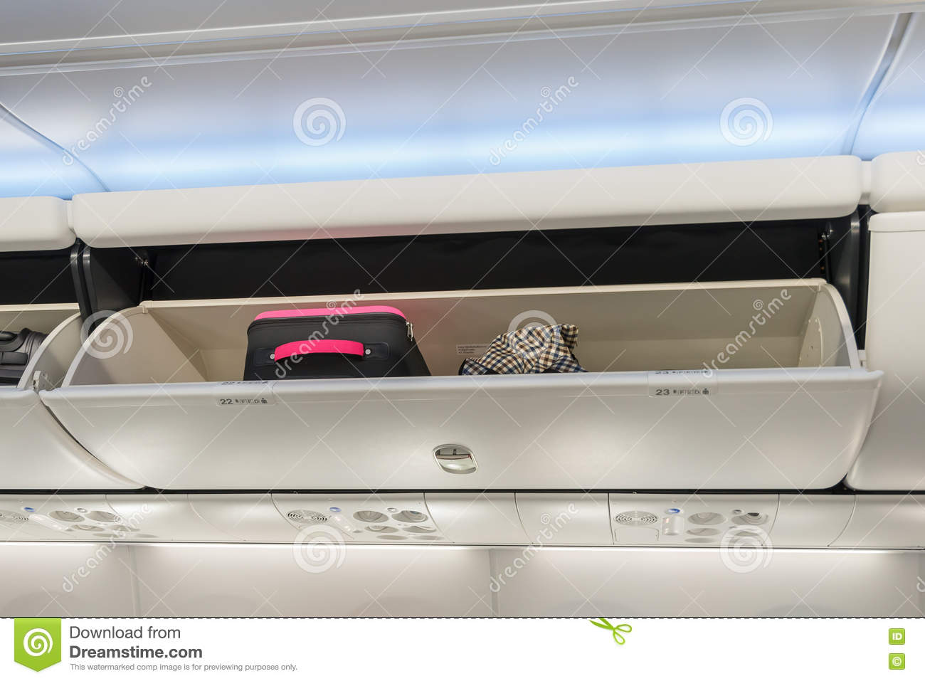 Carry-on luggage in overhead storage compartment on airplane.