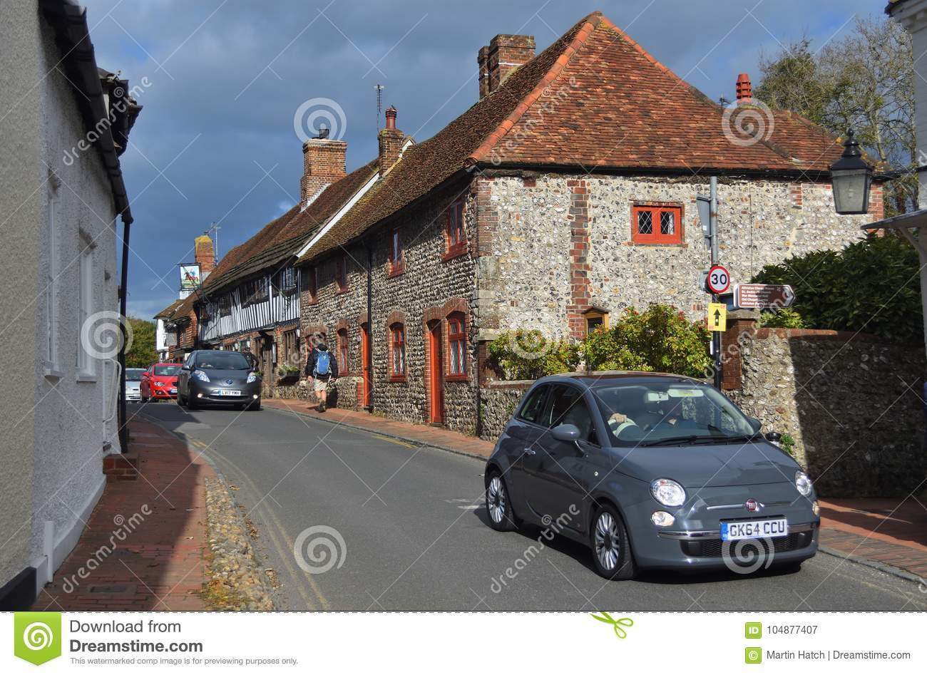 Cars being driven through the narrow streets of picturesque Alfriston East Sussex.