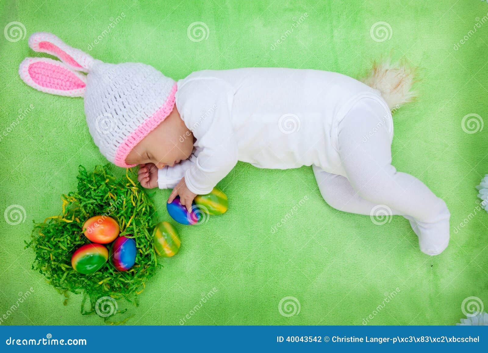 Cartão de Páscoa bonito de um bebê em um equipamento do coelho