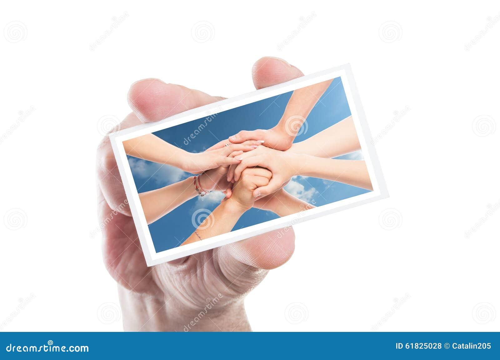 Cartão do voluntário da terra arrendada da mão com mãos juntadas como o fundo