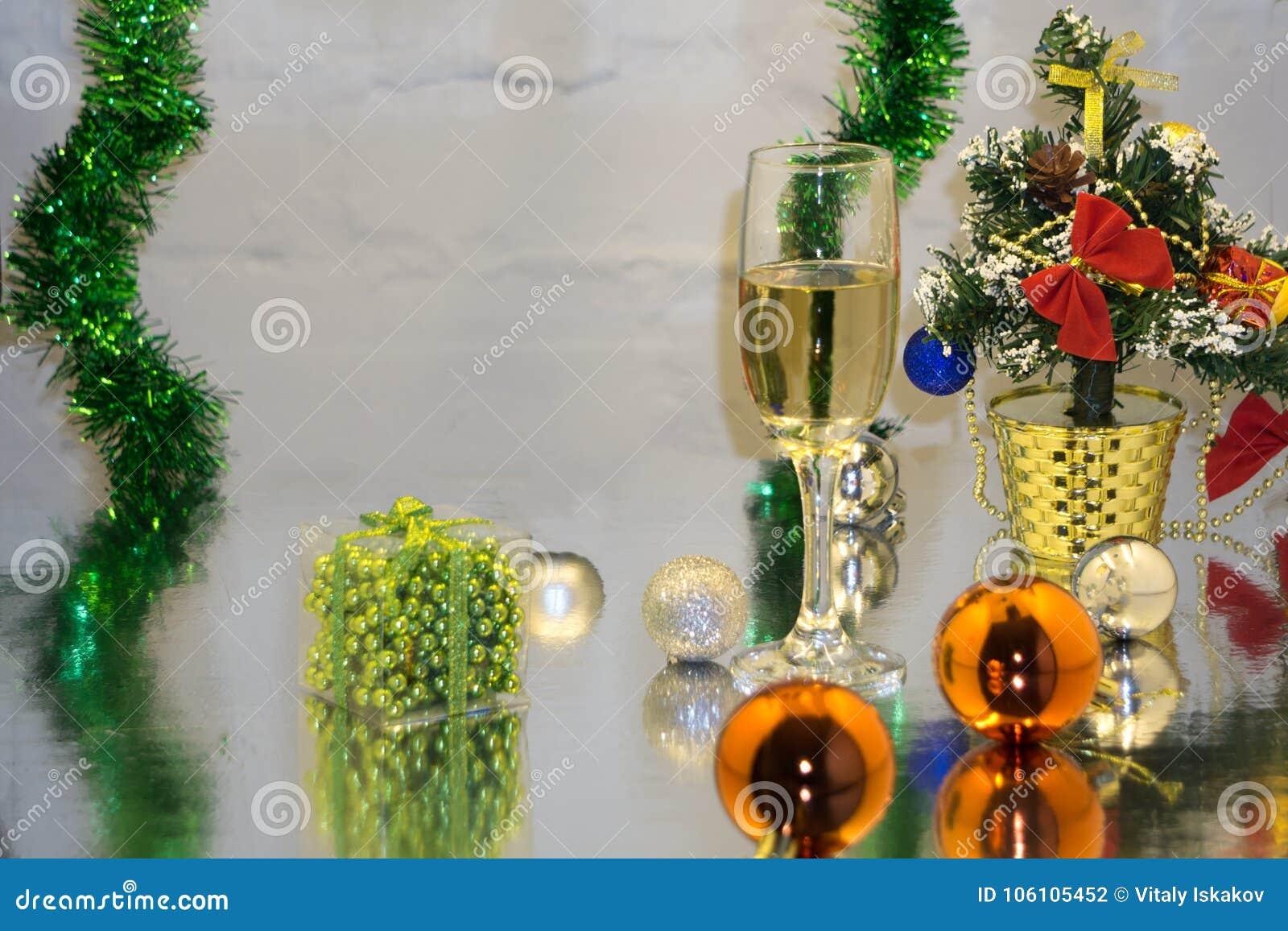 Cartão feito do Natal e as bolas da decoração do ano do teixo, o ouropel, a vela e os dois vidros do champanhe com reflexão, cópi