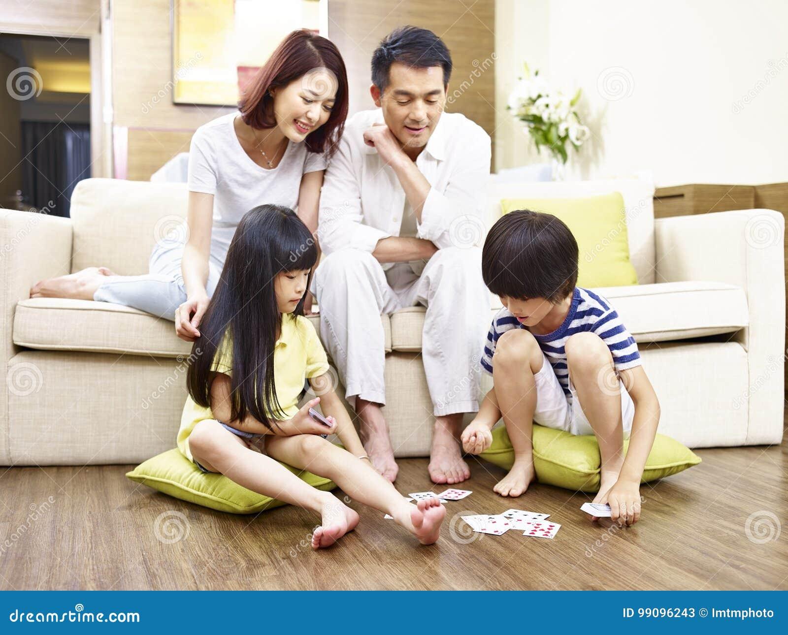 Cartões de jogo asiáticos das crianças quando observação dos pais