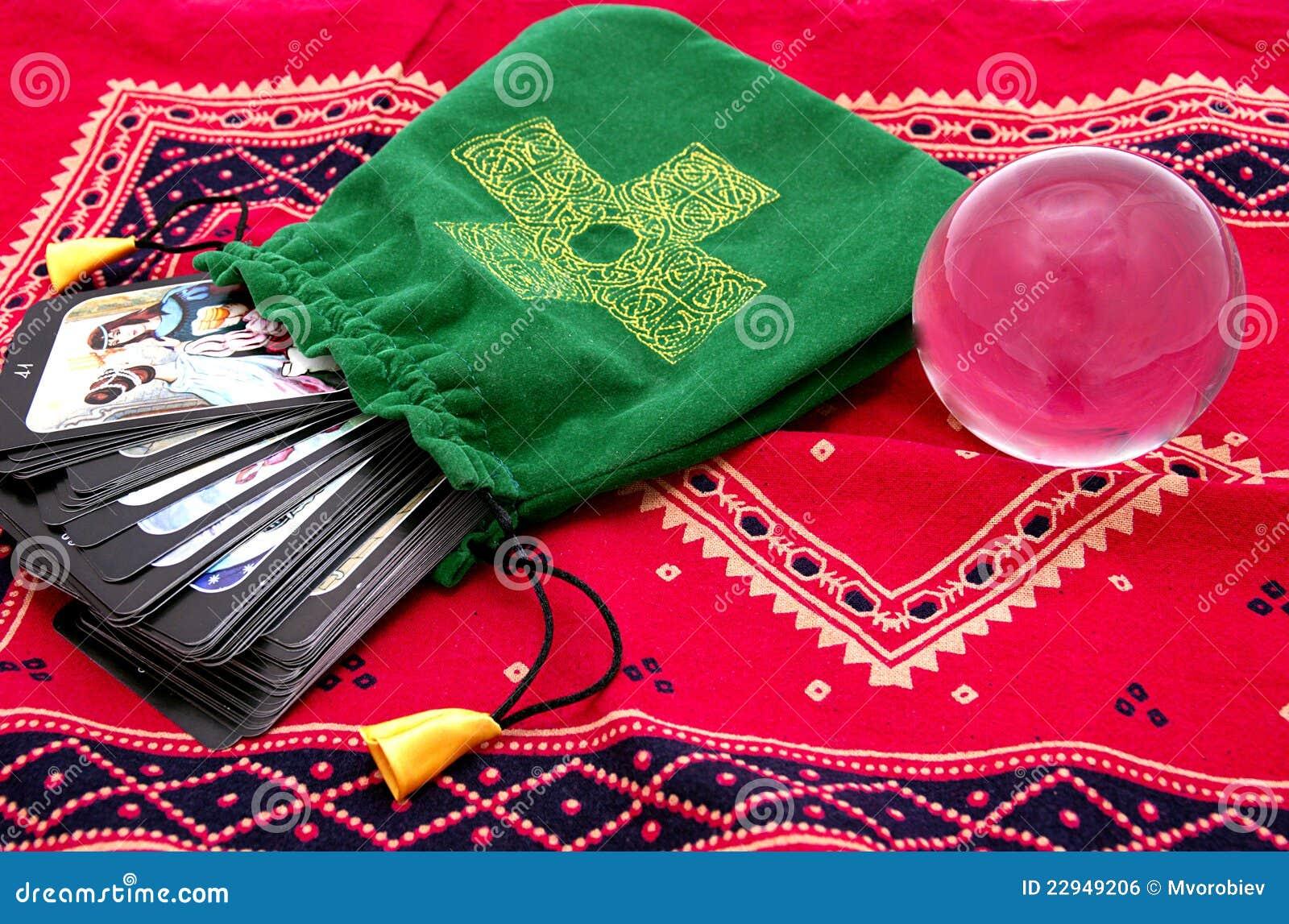 Cartões de Tarot no malote verde e na esfera de cristal