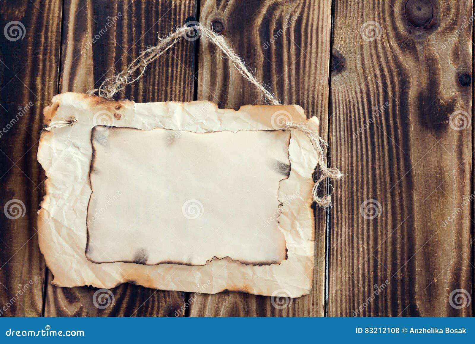 Carta bruciacchiata d attaccatura su un fondo di legno