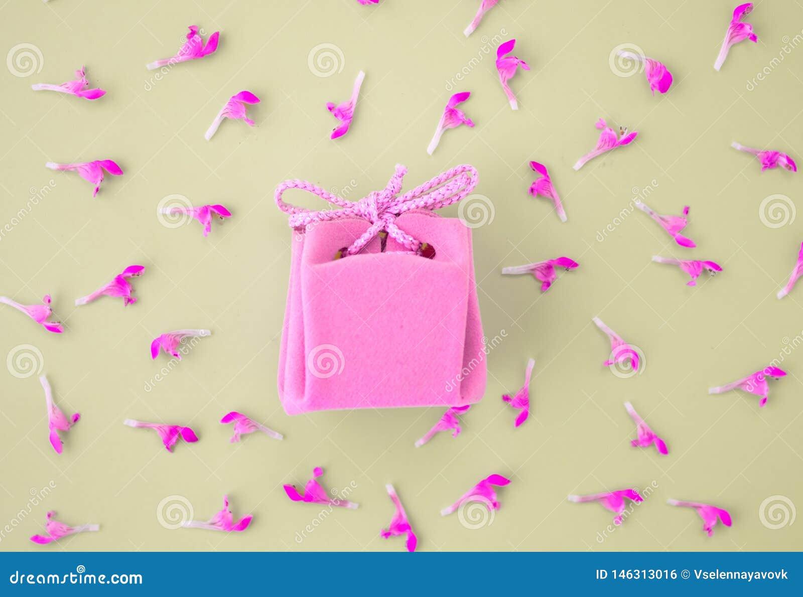 Carta di regalo rosa su un fondo grigio con i fiori Bello regalo delicato