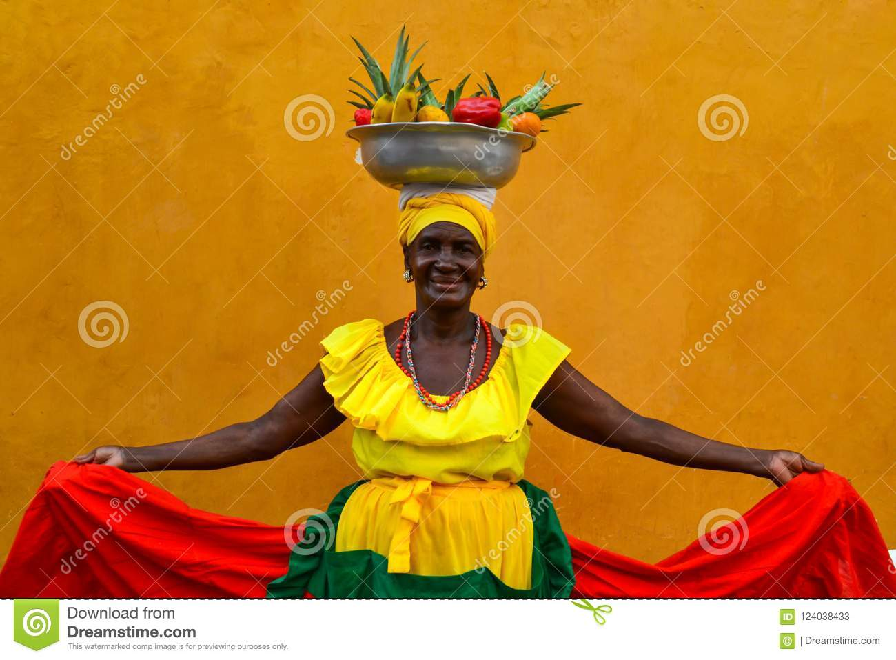 CARTAGENA DE INDIAS, COLOMBIA - July 27, 2017: Beautiful smiling woman wearing traditional costume sell fruits in the center of Ca