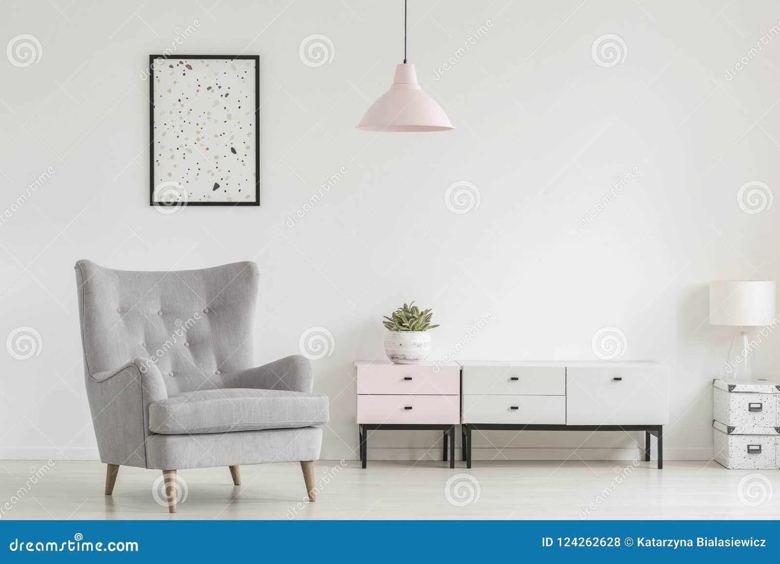 Cartaz acima da poltrona e da lâmpada cinzentas no interio branco da sala de visitas