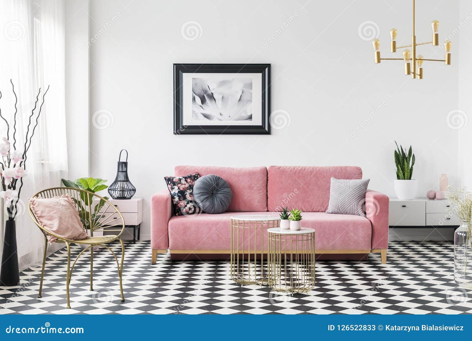 Cartaz acima do sofá cor-de-rosa no interior da sala de visitas com a poltrona do ouro no assoalho quadriculado Foto real