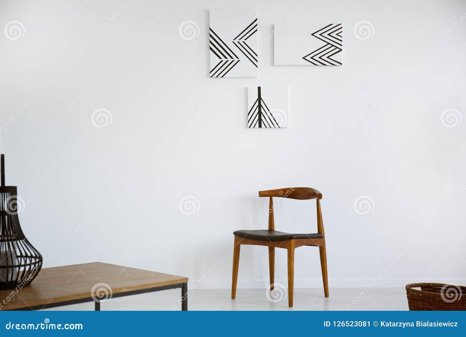 Cartazes na parede branca acima da cadeira de madeira no interior mínimo da sala de visitas com tabela Foto real