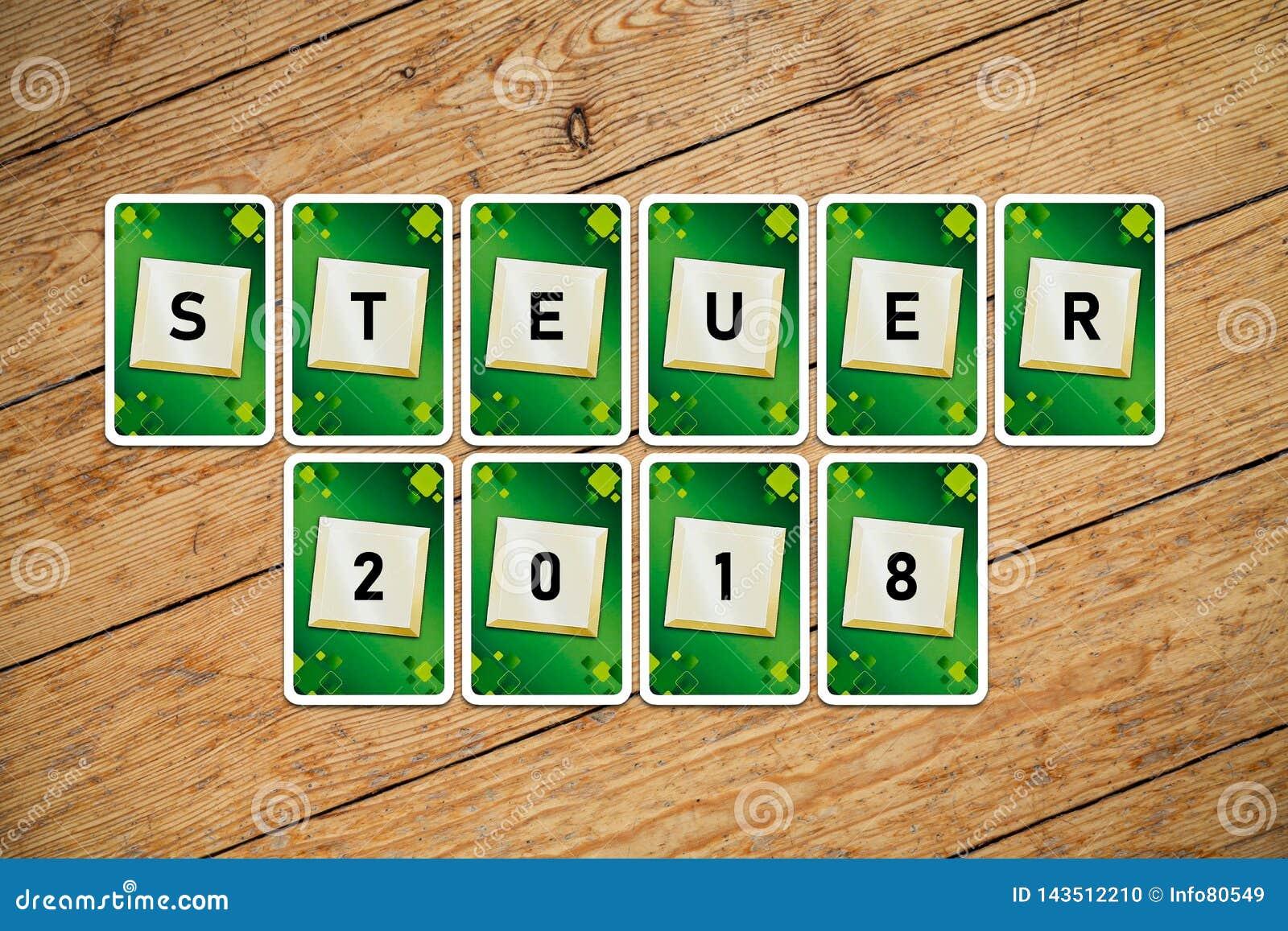 """Carte da gioco con testo """"Steuer 2018 """"su un pavimento di legno"""