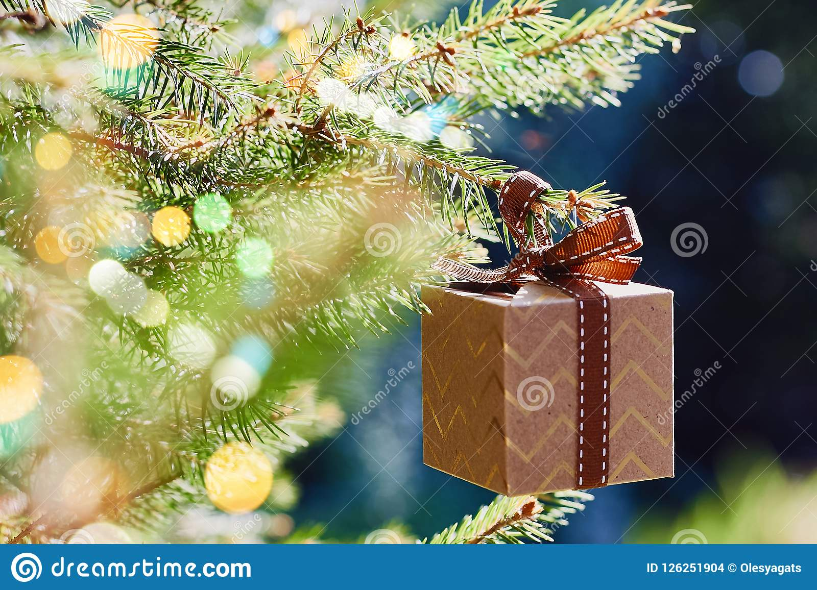 Carte de vacances de Noël et de nouvelle année Boîte-cadeau accrochant sur la branche d arbre de Noël sur le fond de vert bleu
