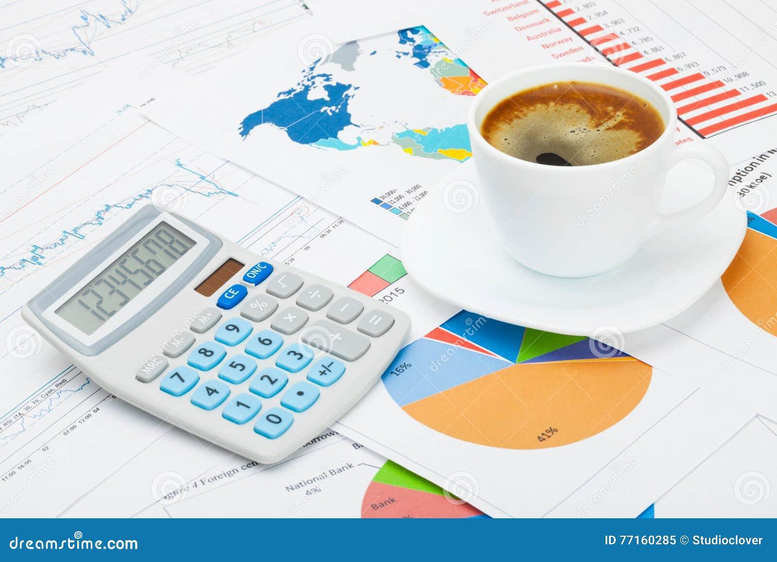 Carte du monde et quelques diagrammes sous la tasse et la calculatrice de café