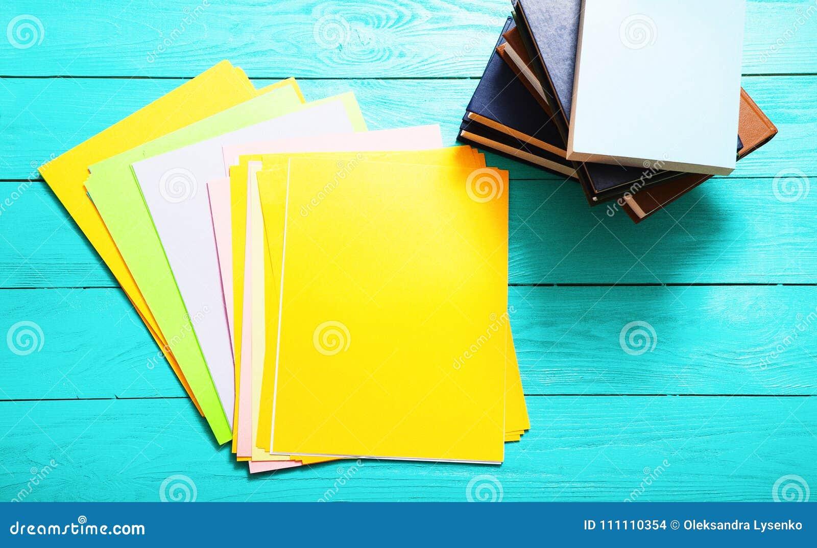 Carte variopinte con lo spazio della copia e molti libri sulla tavola di legno blu Vista superiore